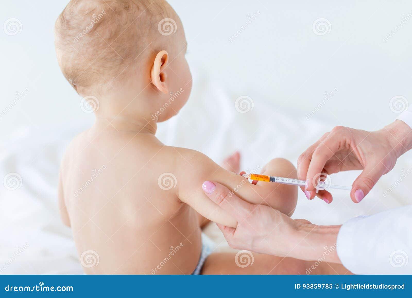 Colpo potato del lavoratore medico che fa iniezione per il neonato sveglio