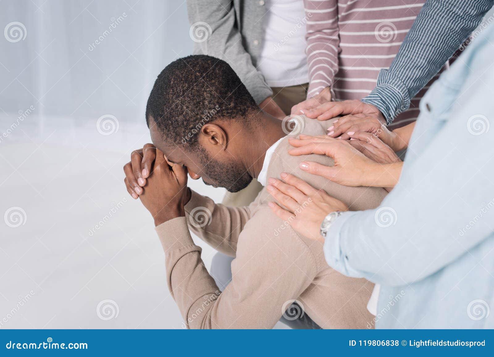 Colpo potato dell uomo afroamericano depresso sostenente della gente