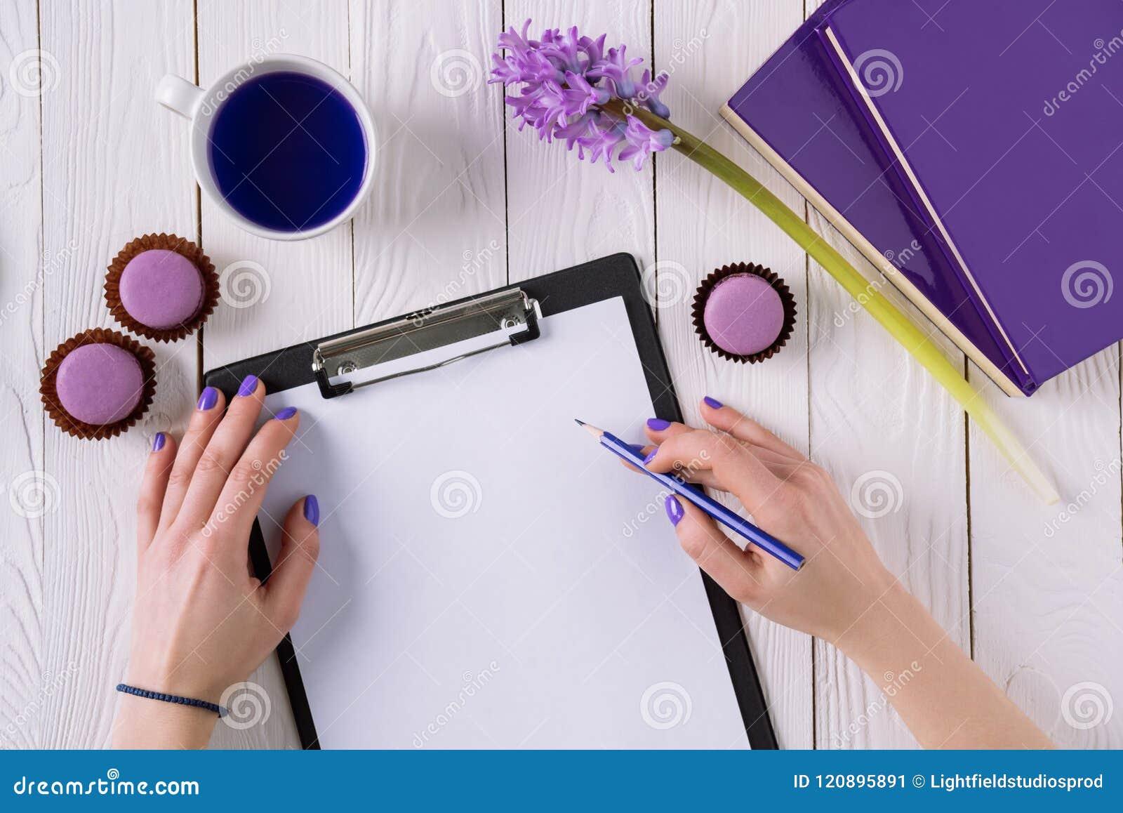 Colpo potato di scrittura della donna nella carta sulla lavagna per appunti
