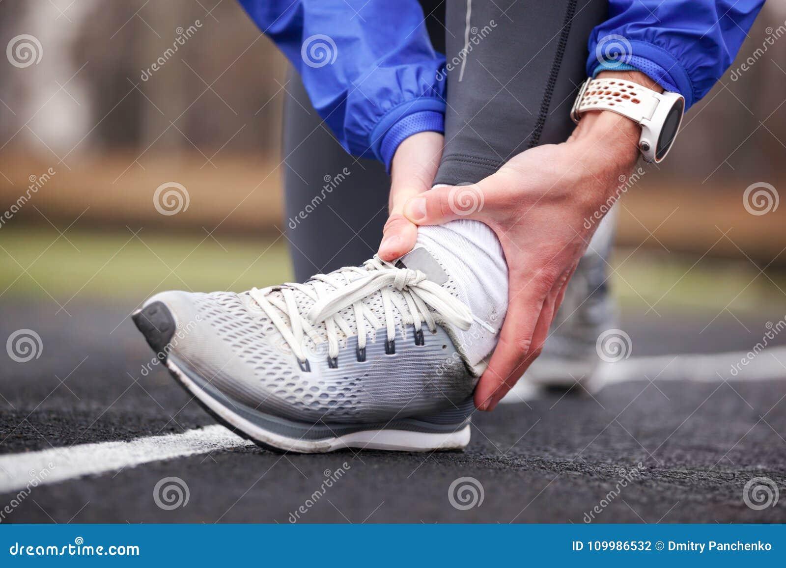 Colpo potato di un giovane che tiene la sua caviglia nella distorsione di dolore una f