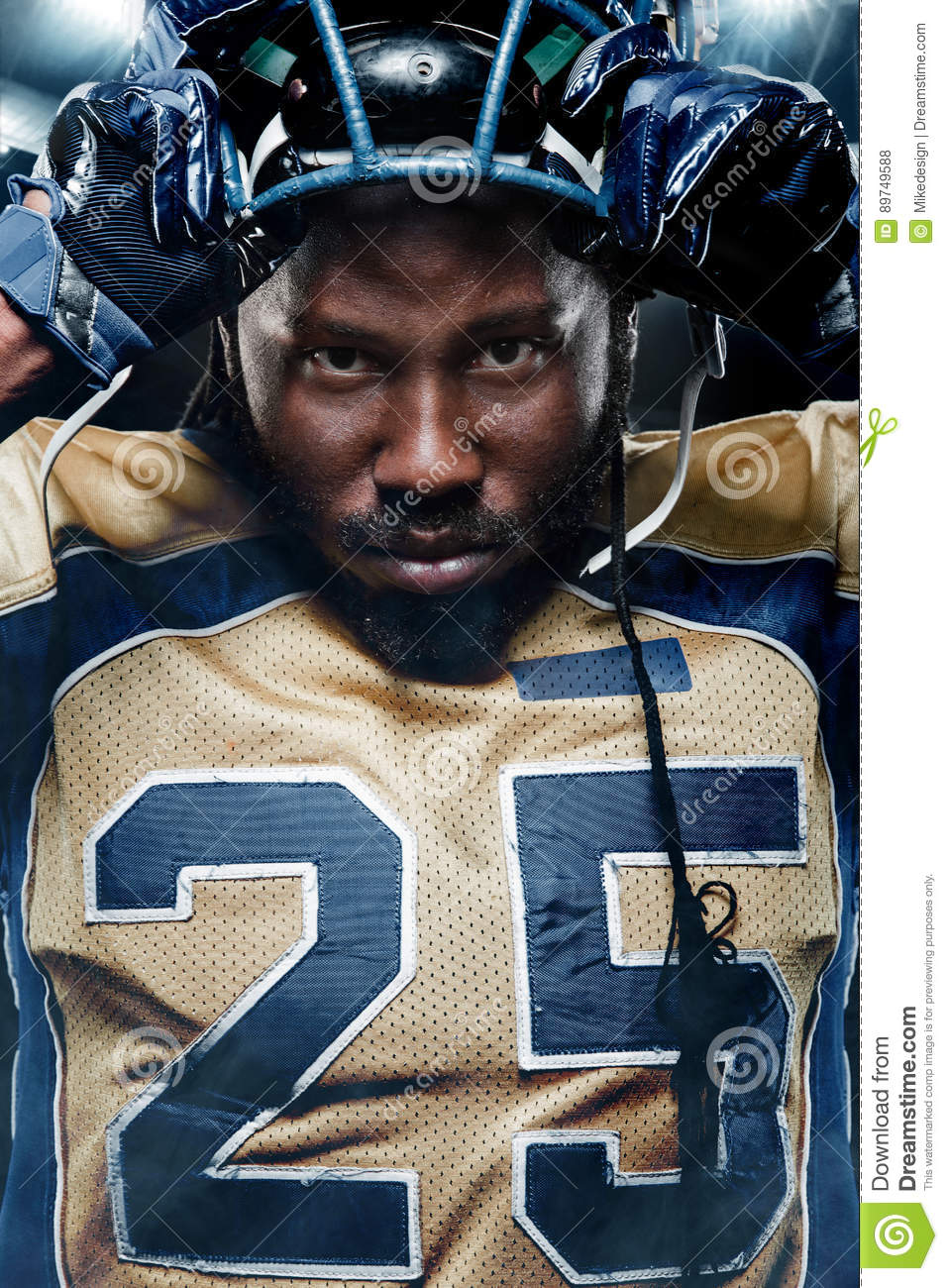 Colse-up portrait of american football player on stadium with lights on background