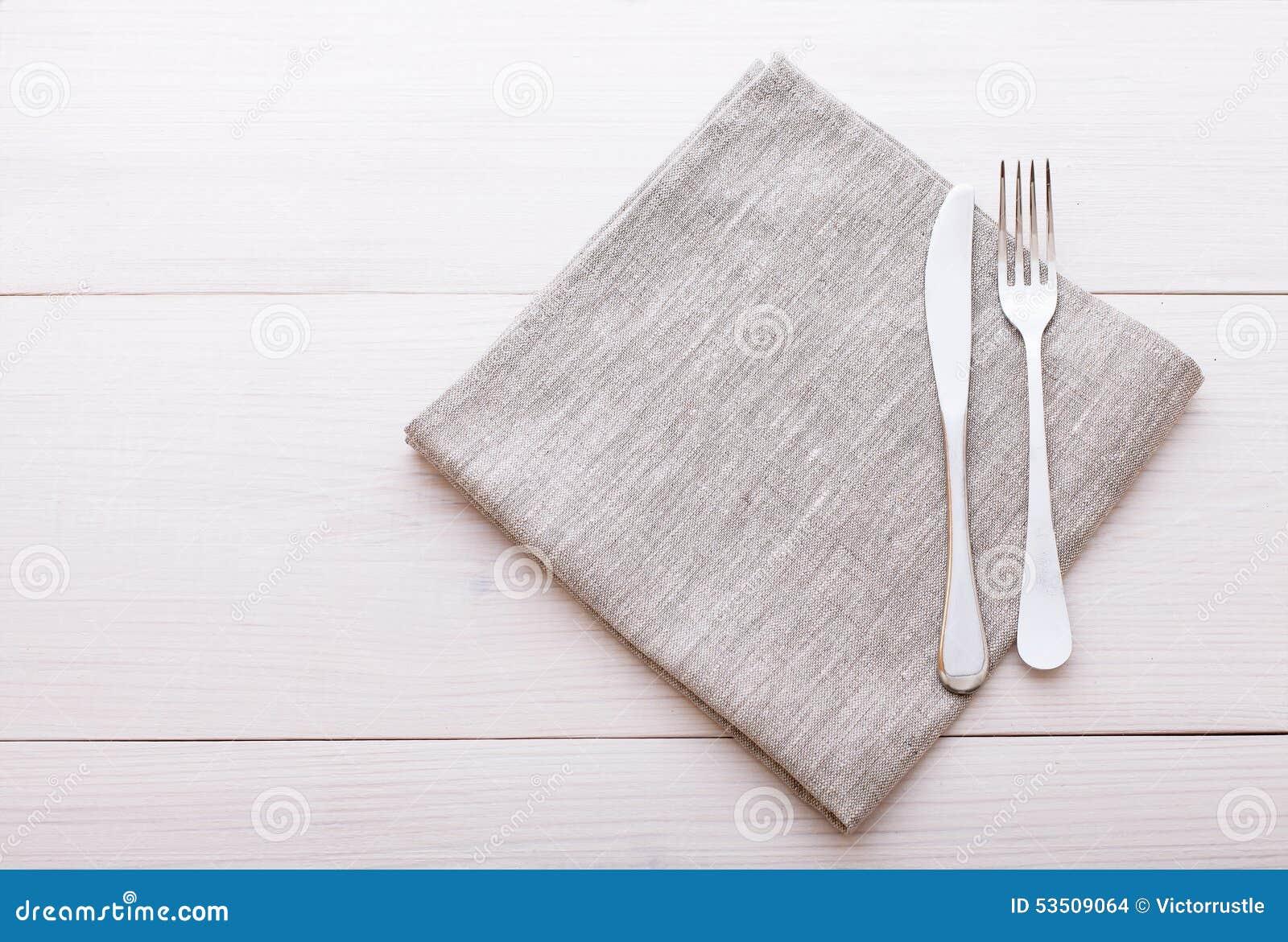 Coltelleria, tovaglia sulla tavola di legno bianca per