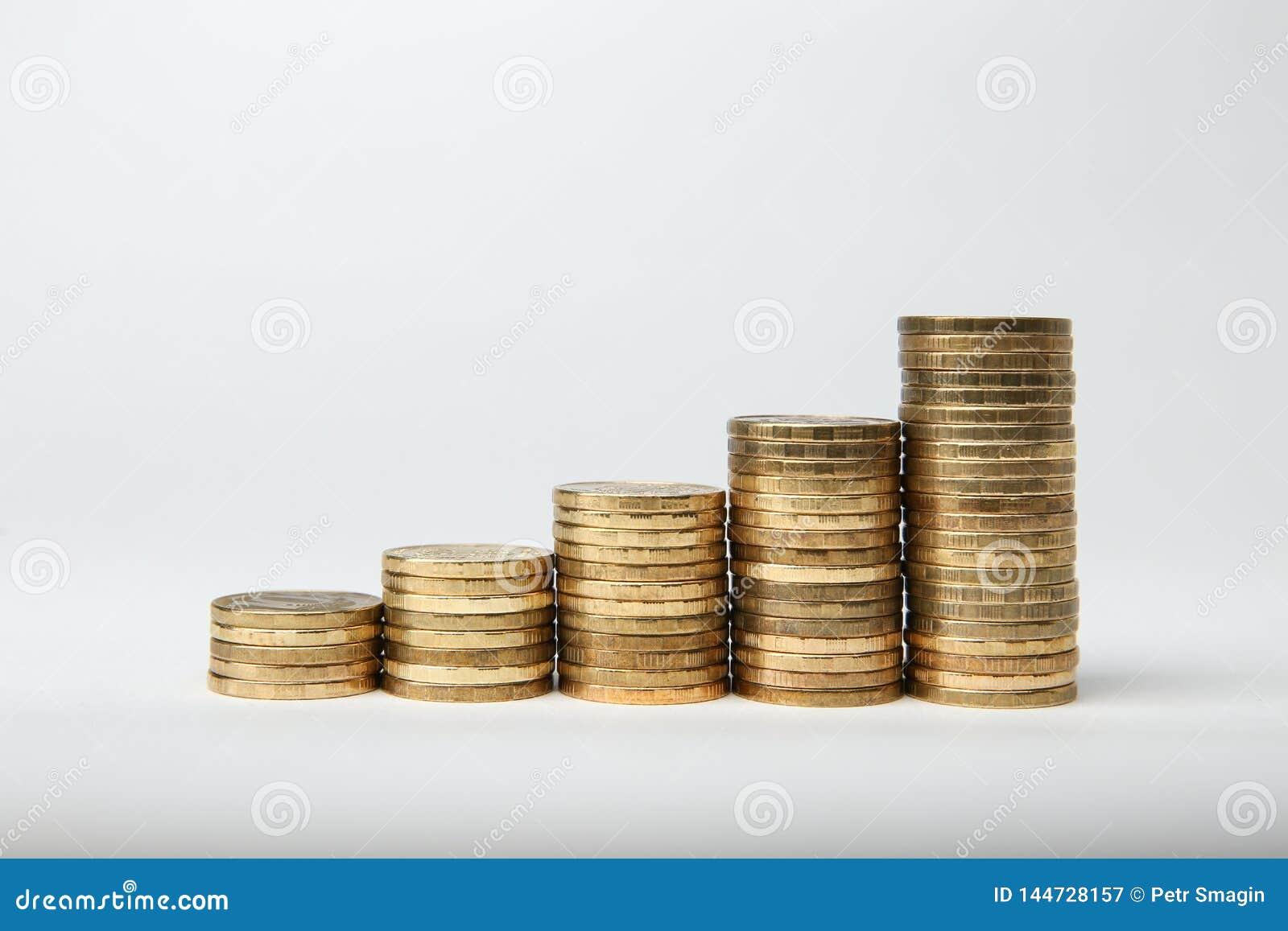 Columnas de las monedas de oro aisladas en el fondo blanco