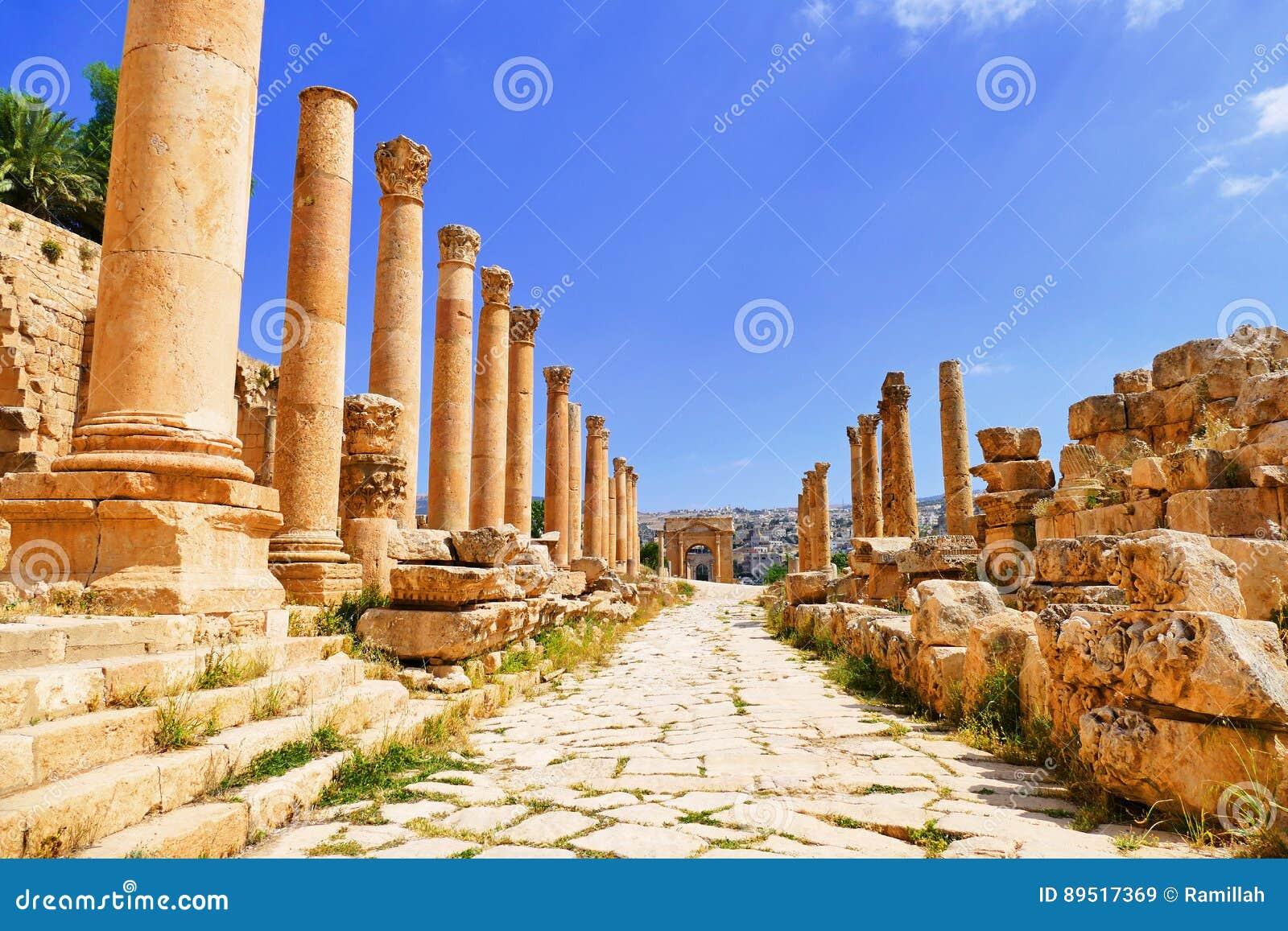 Colunas greco-romanas antigas do Corinthian da vista cênico em Cardo Colonnaded ao Tetrapylon norte em Jerash, Jordânia