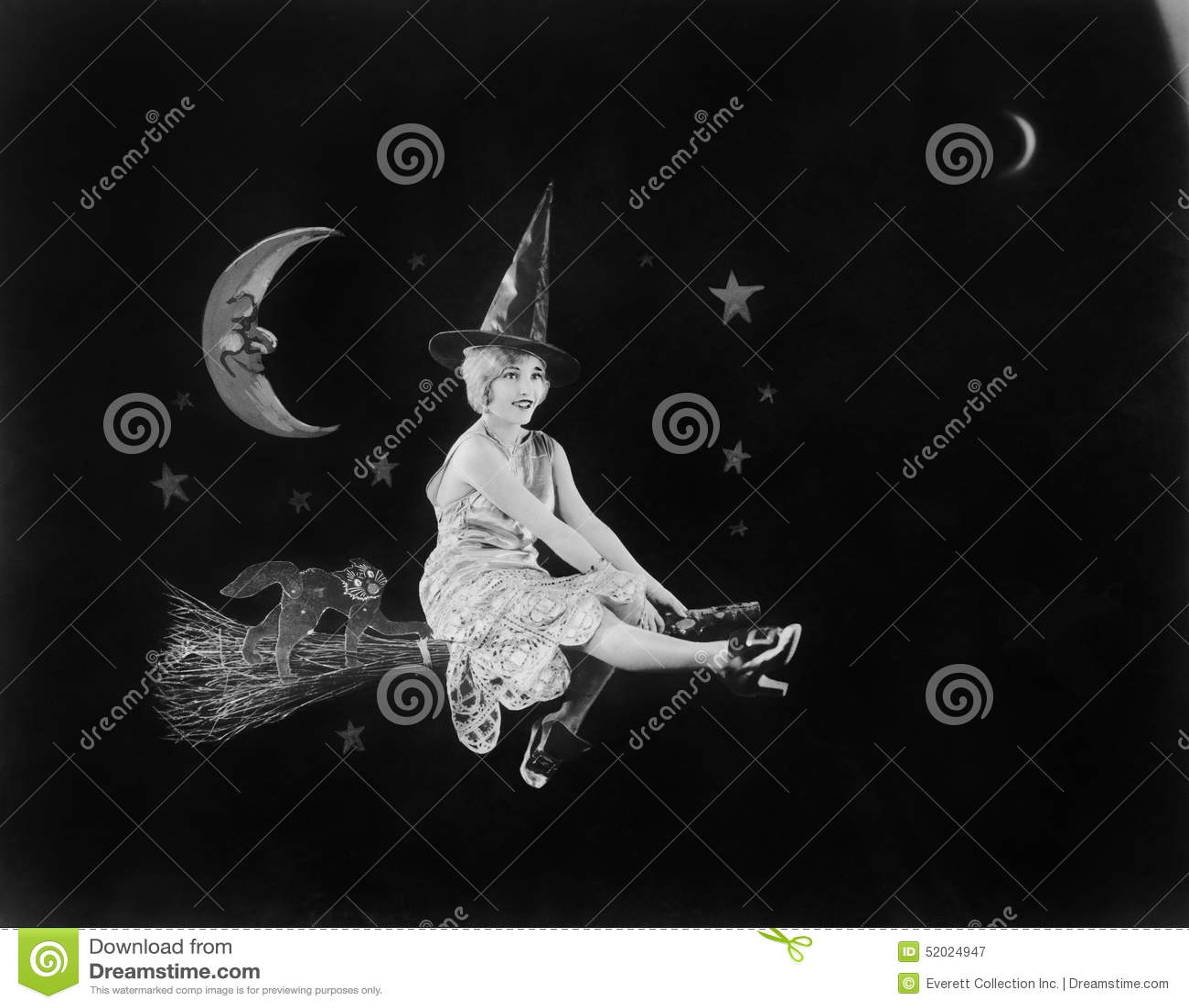 Com o homem na lua e em uma bruxa em uma vassoura, um voo da fantasia ilumina o céu noturno (todas as pessoas descritas não são u