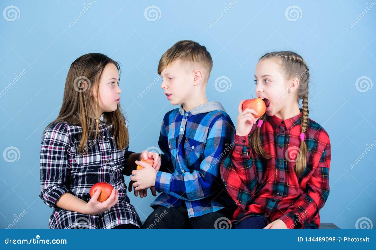Coma la fruta y ser sano Promover la nutrición sana El muchacho y los amigos de muchachas comen la manzana Adolescencias con boca