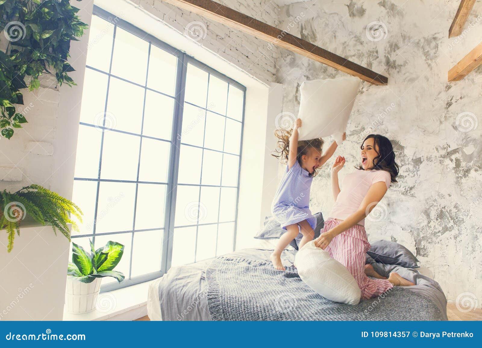Combat d oreiller de mère et de fille dans la chambre à coucher
