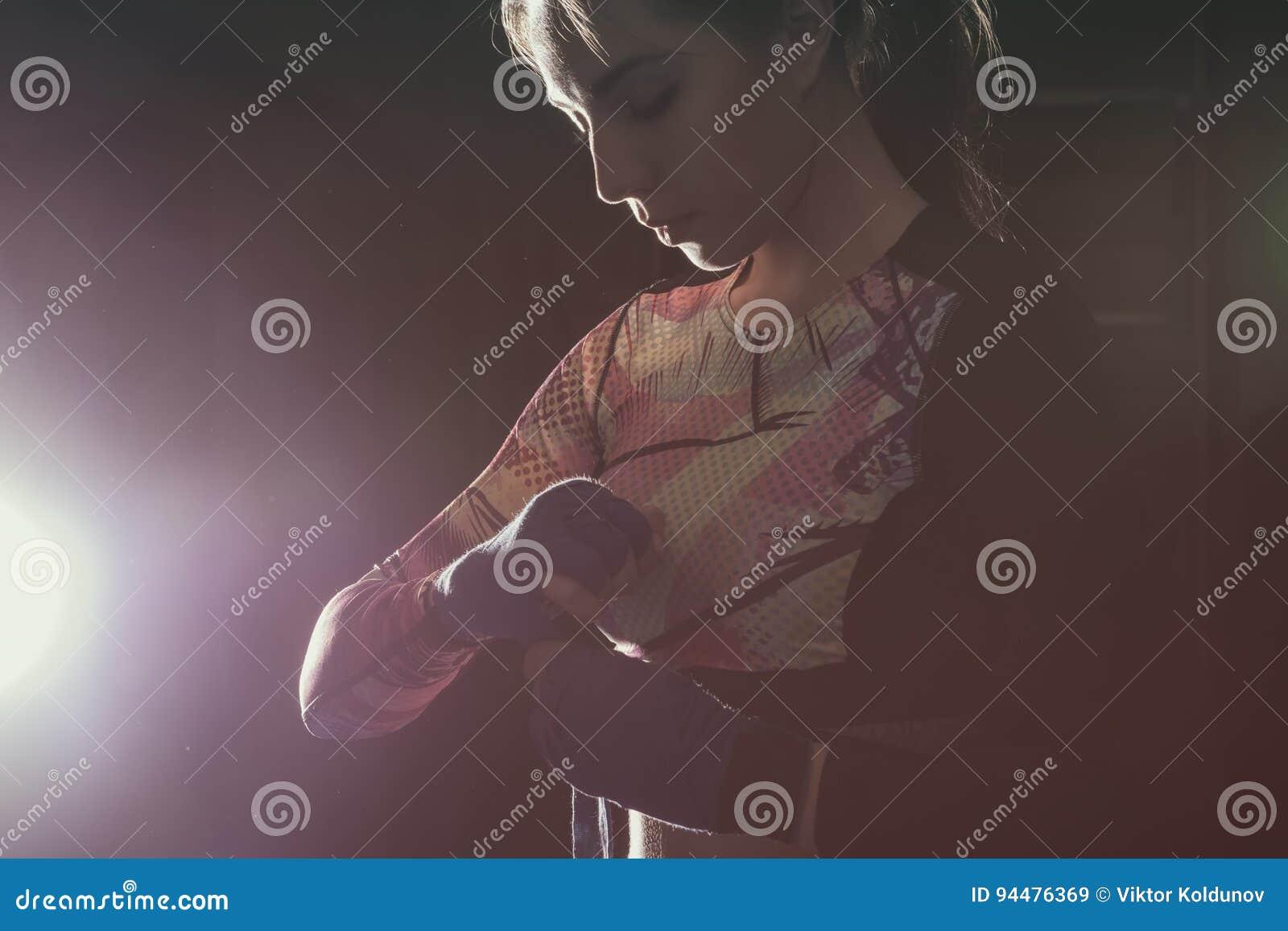 Combattente femminile che indossa i guantoni da pugile che prepairing per prepararsi