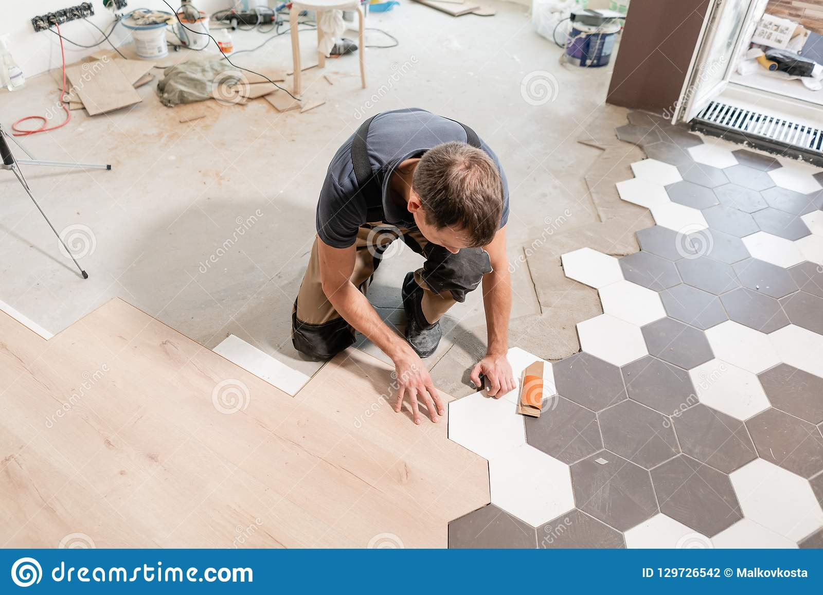 Male worker installing new wooden laminate flooring. The combination of wood panels of laminate and ceramic tiles in the