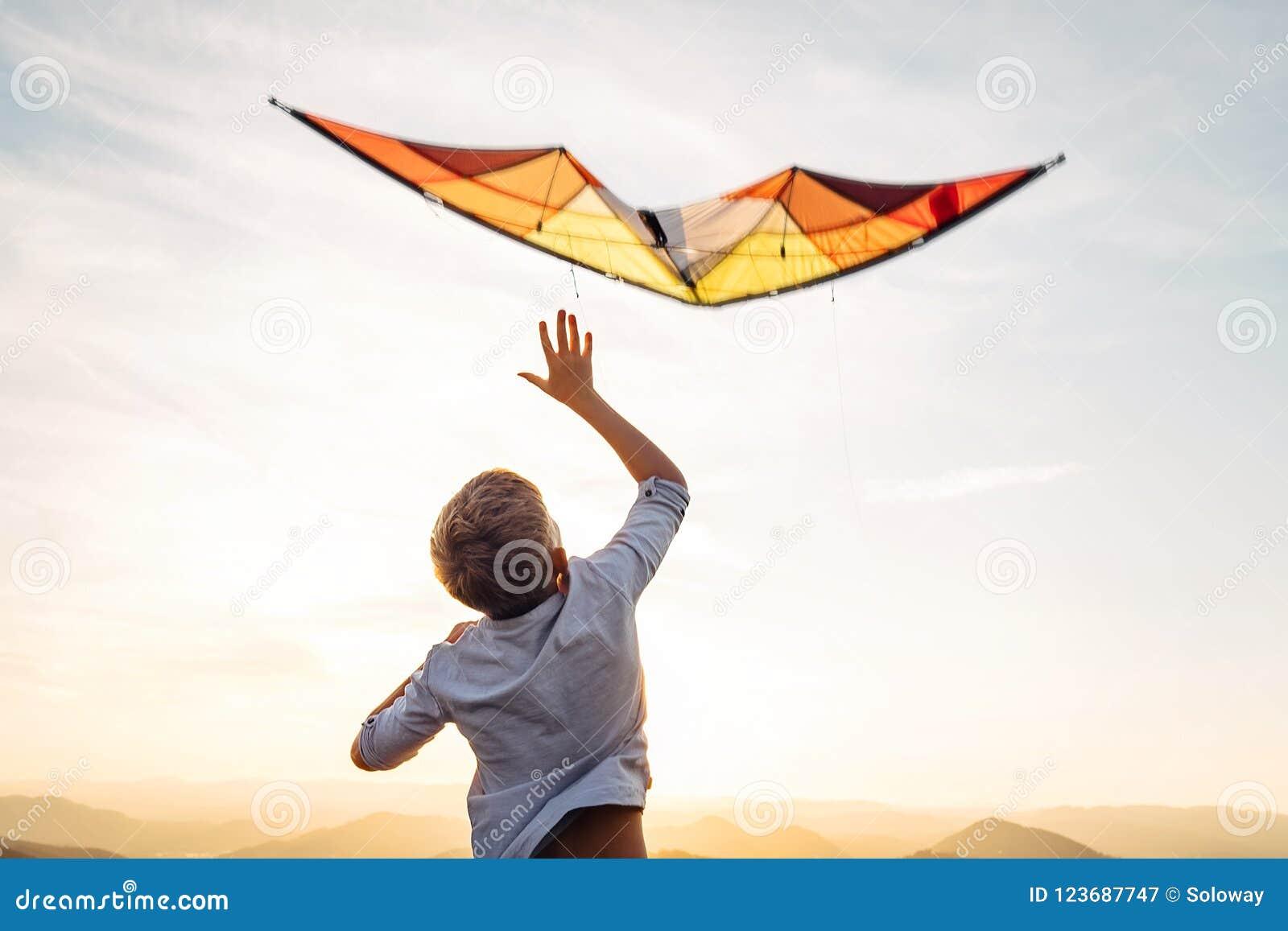 Começo do menino para voar o papagaio alaranjado brilhante no céu