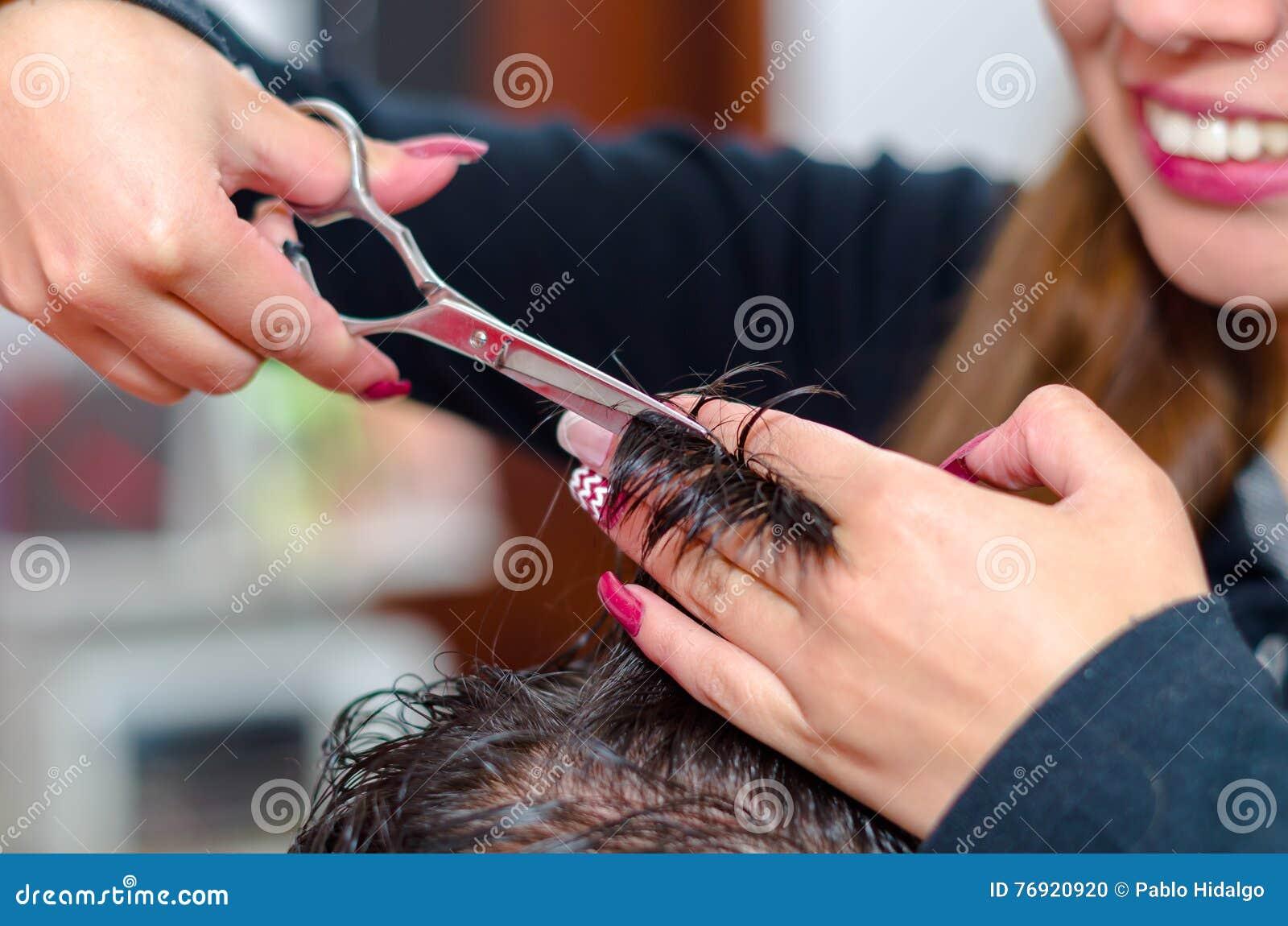 Come fare un taglio di capelli piacevole, capelli fra le dita e le forbici
