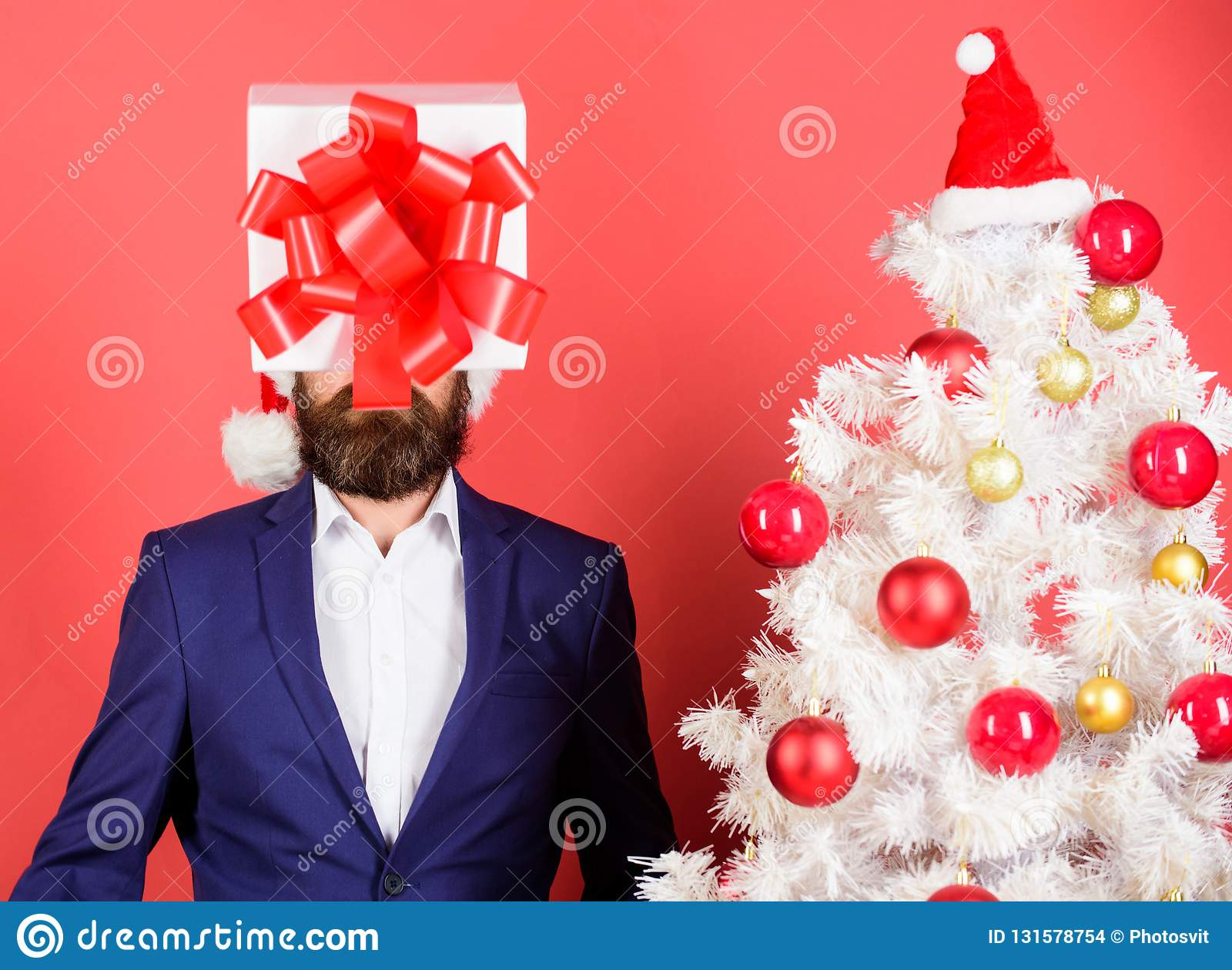 Come up with good present. Gift service. Head downtrodden with thoughts what to gift. Man bearded formal suit carry gift