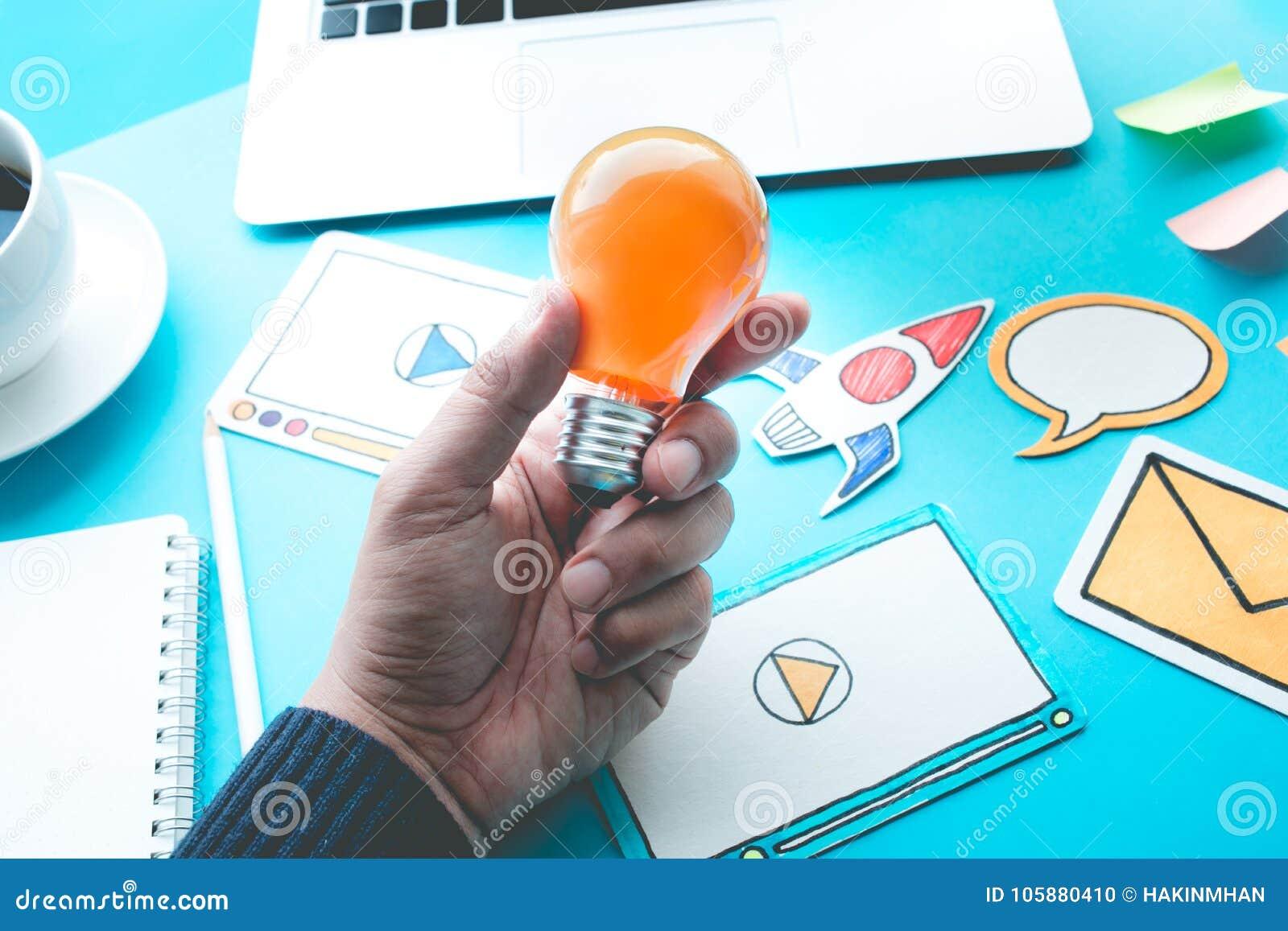 Comece acima conceitos da ideia com a ampola na mão masculina