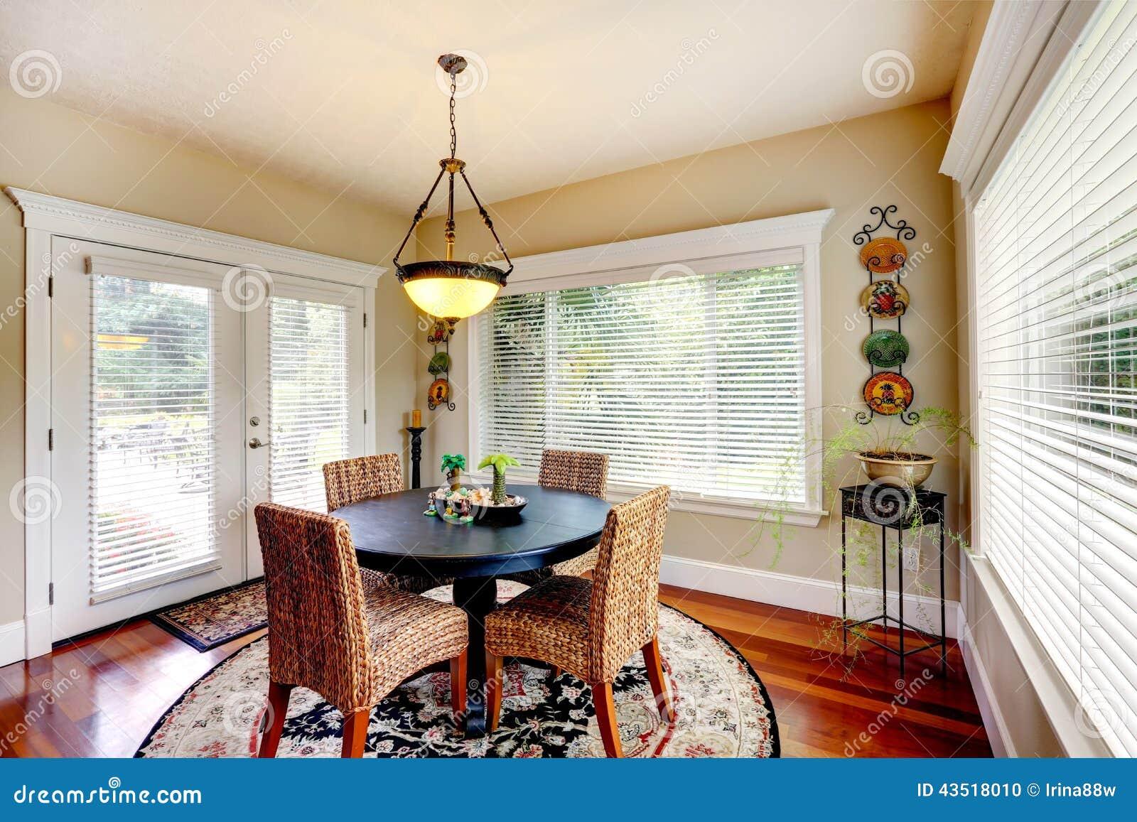 Comedor con la tabla negra redonda y las sillas de mimbre for Sillas mimbre comedor