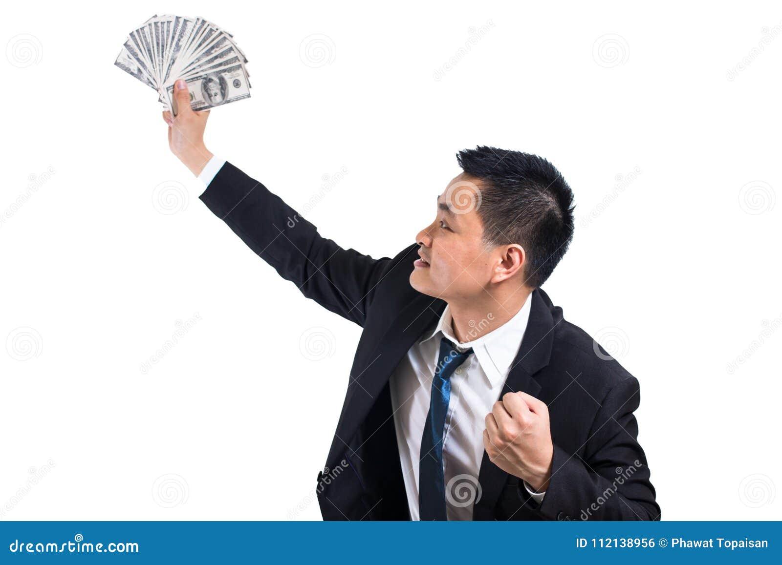 Comemoração asiática nova do homem de negócios bem sucedida Homem de negócios que mantém cédulas do dólar feliz e sorriso
