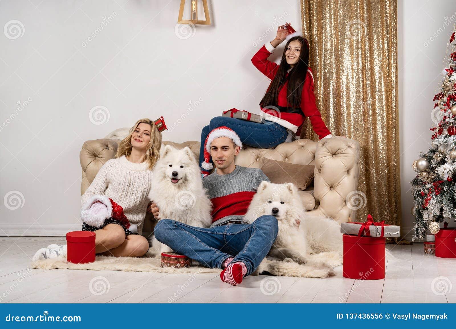 Comemoração do Natal feliz de jovens com cães e presentes