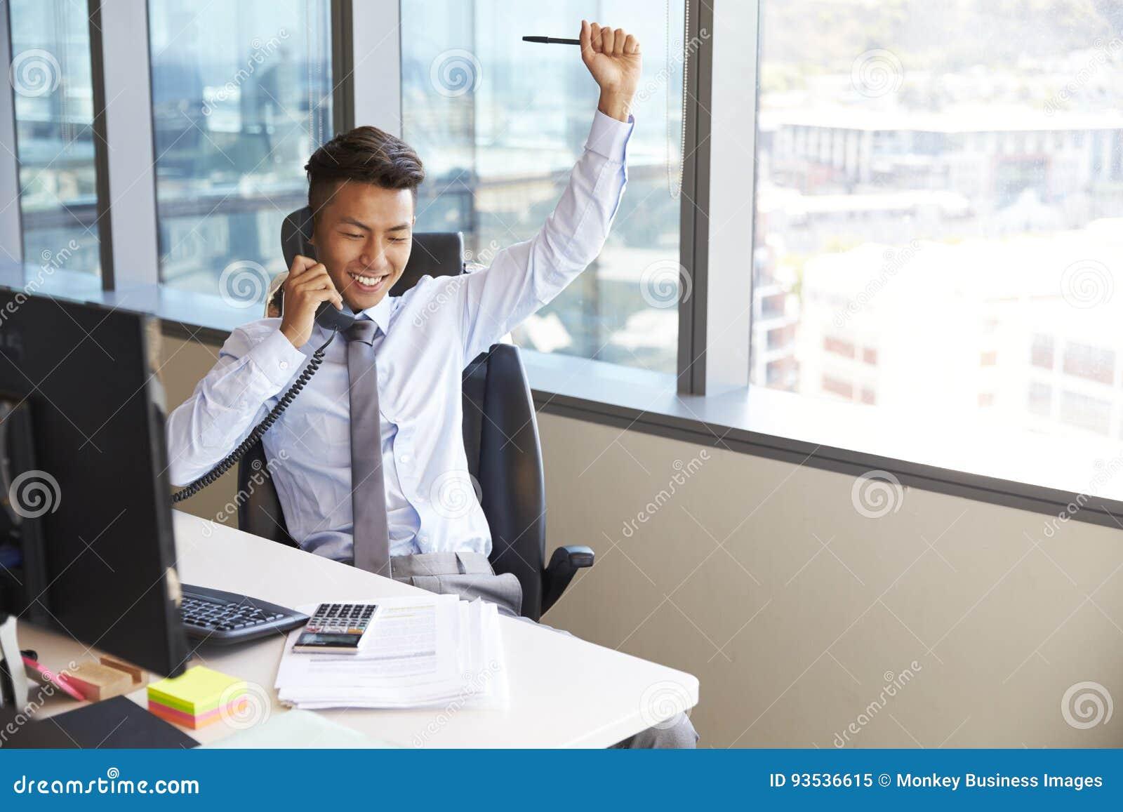 Comemorando o homem de negócios Making Phone Call na mesa no escritório