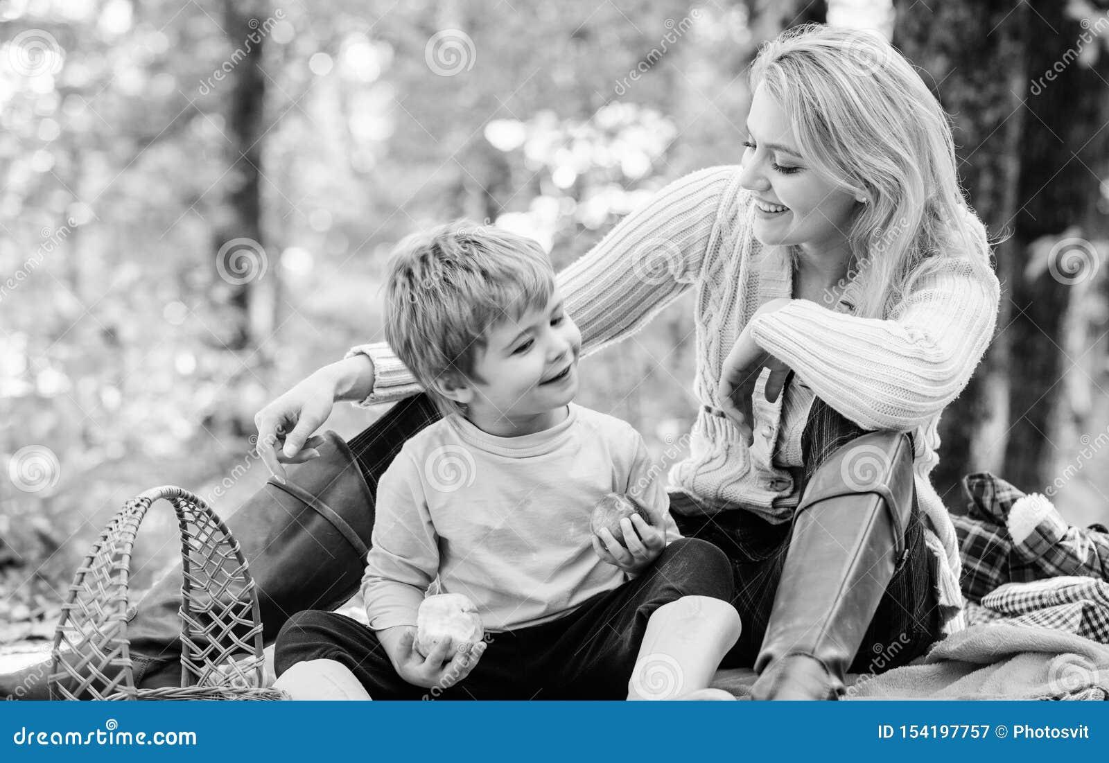 Comendo o petisco durante a caminhada Inf?ncia feliz Menino da mam? e da crian?a que relaxa ao caminhar o piquenique da fam?lia d