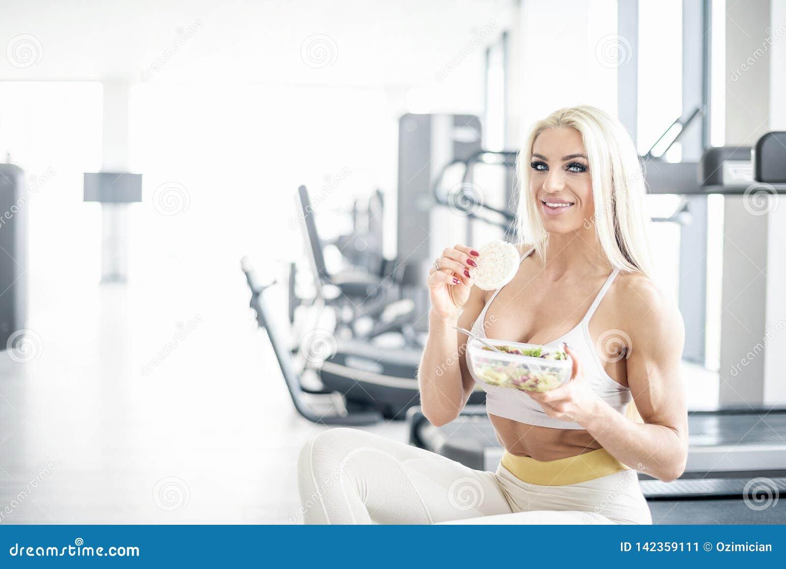 Comer louro da mulher saudável no gym
