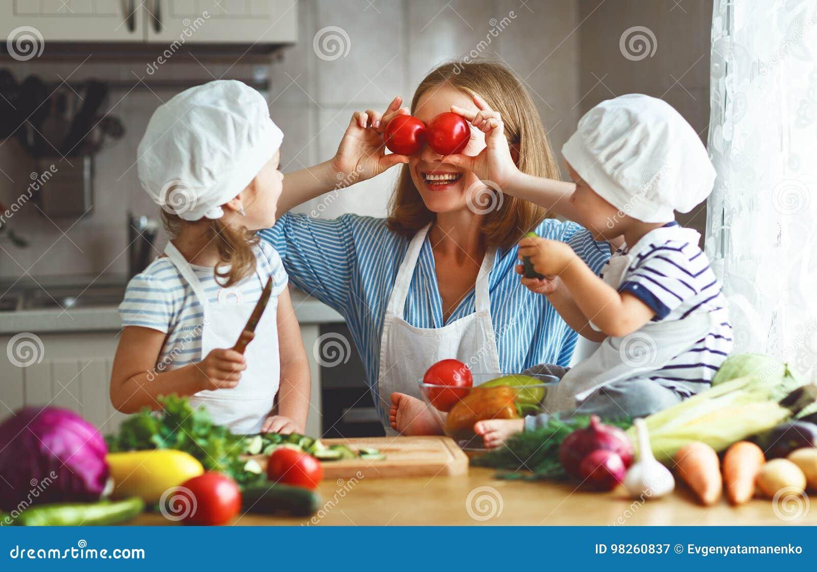 Comer saudável A mãe e as crianças felizes da família preparam o veget