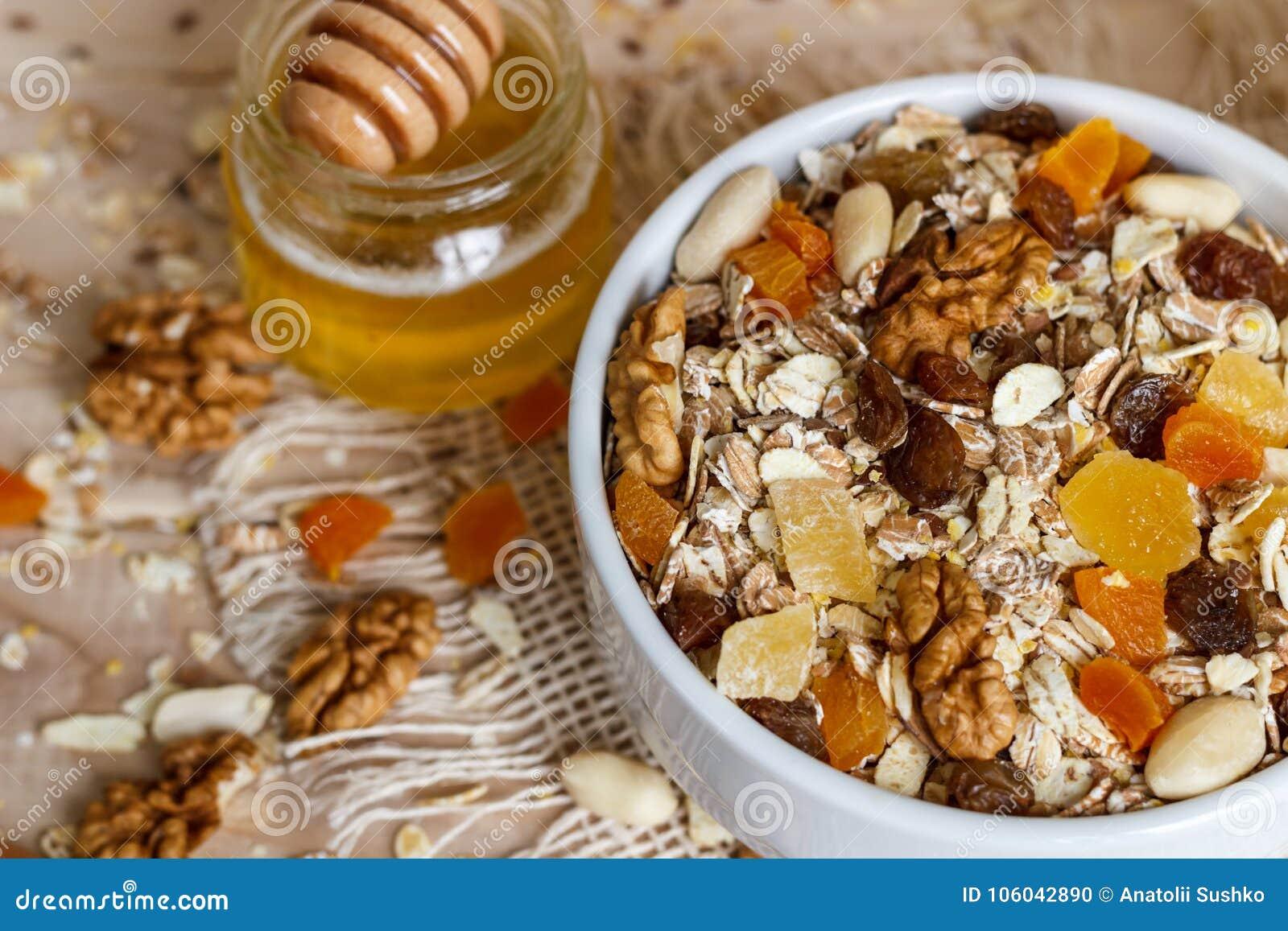 Comer saudável Na placa de madeira é o muesli, mel em um frasco,
