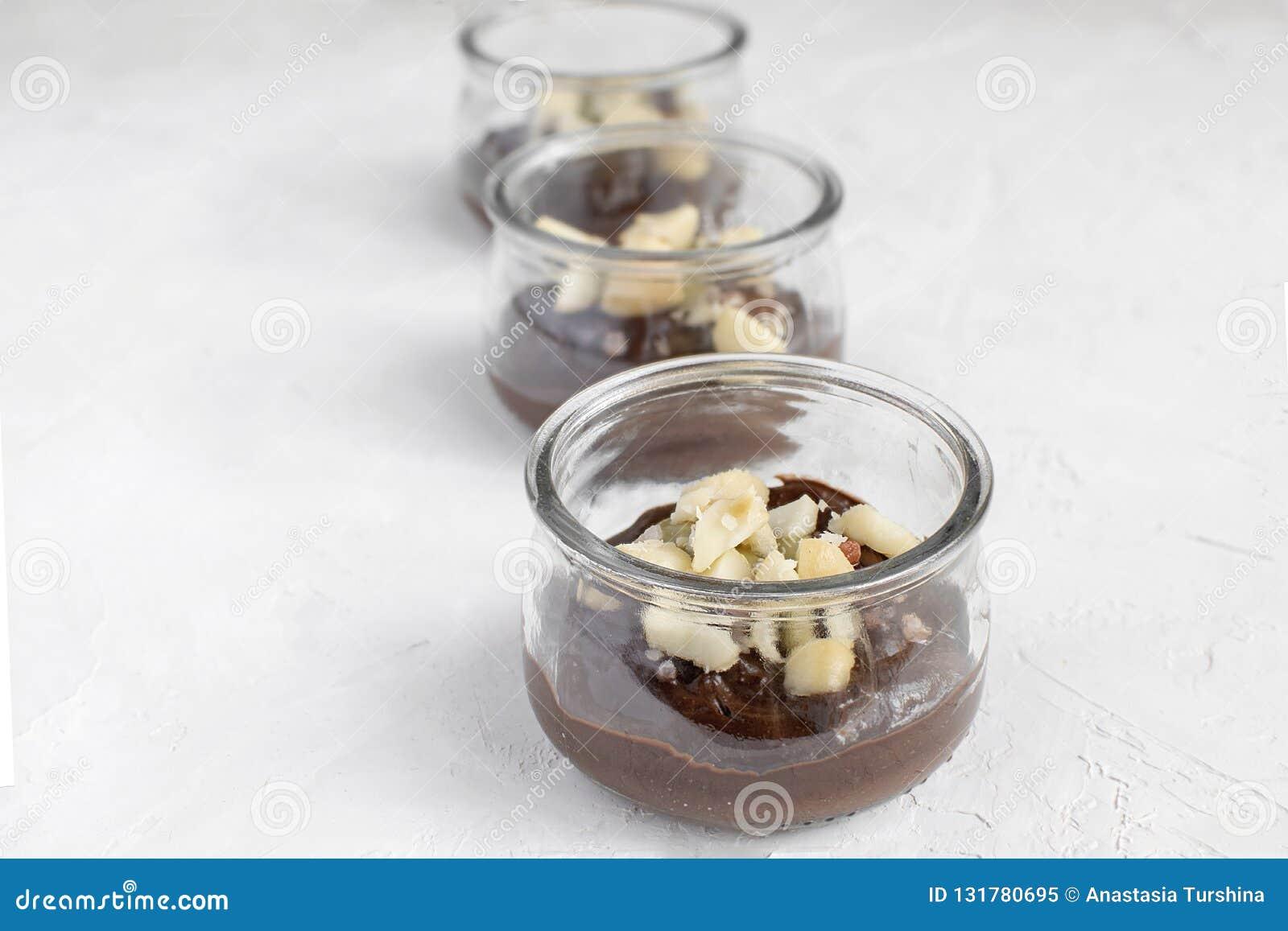 Comer saudável - pudim de chocolate do vegetariano feito do abacate no frasco de vidro com as porcas de macadâmia na parte superi