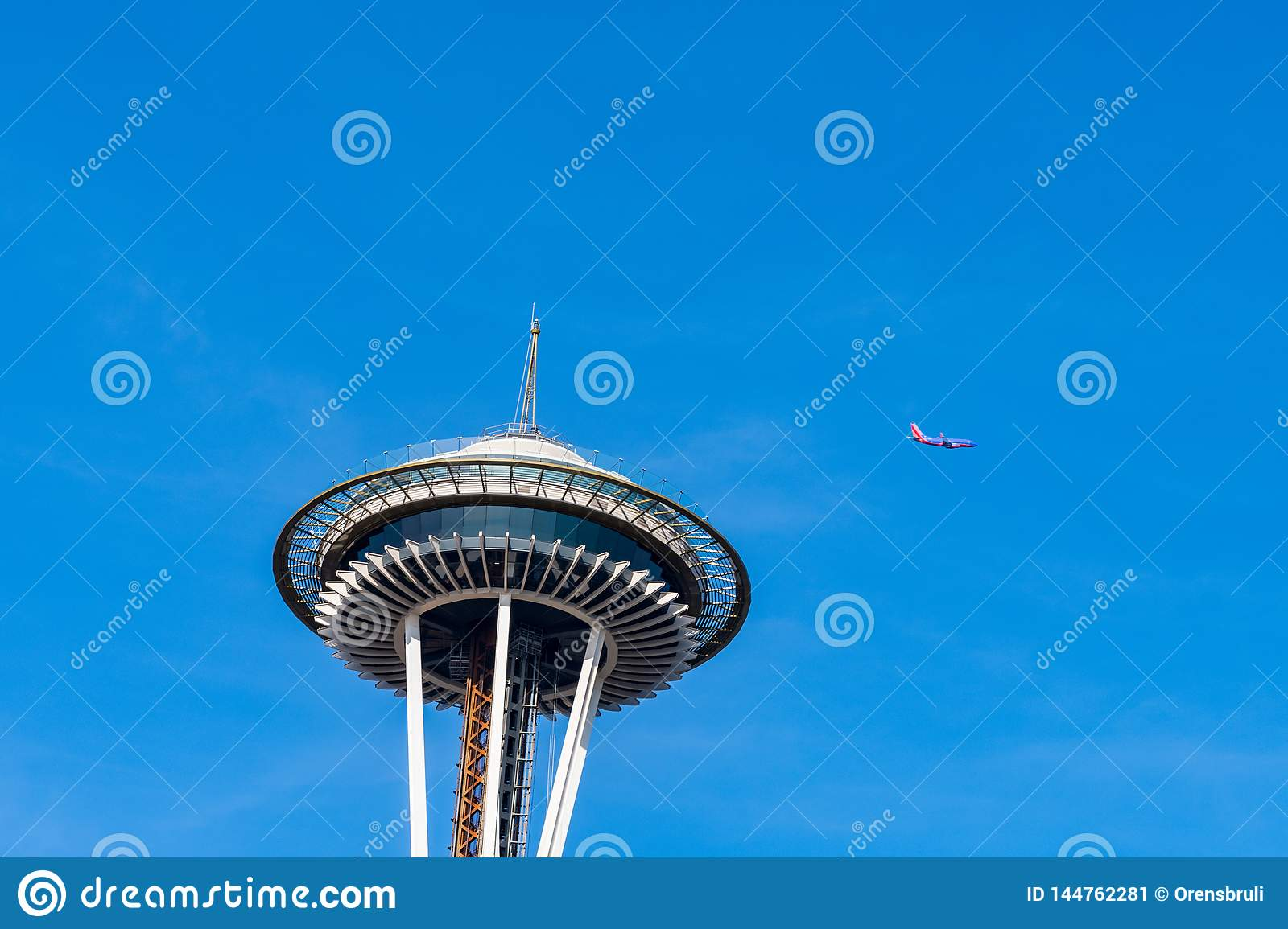 A comercial plane flies over the Space Needle in Seattle A comercial plane flies over the Space Needle in Seattle