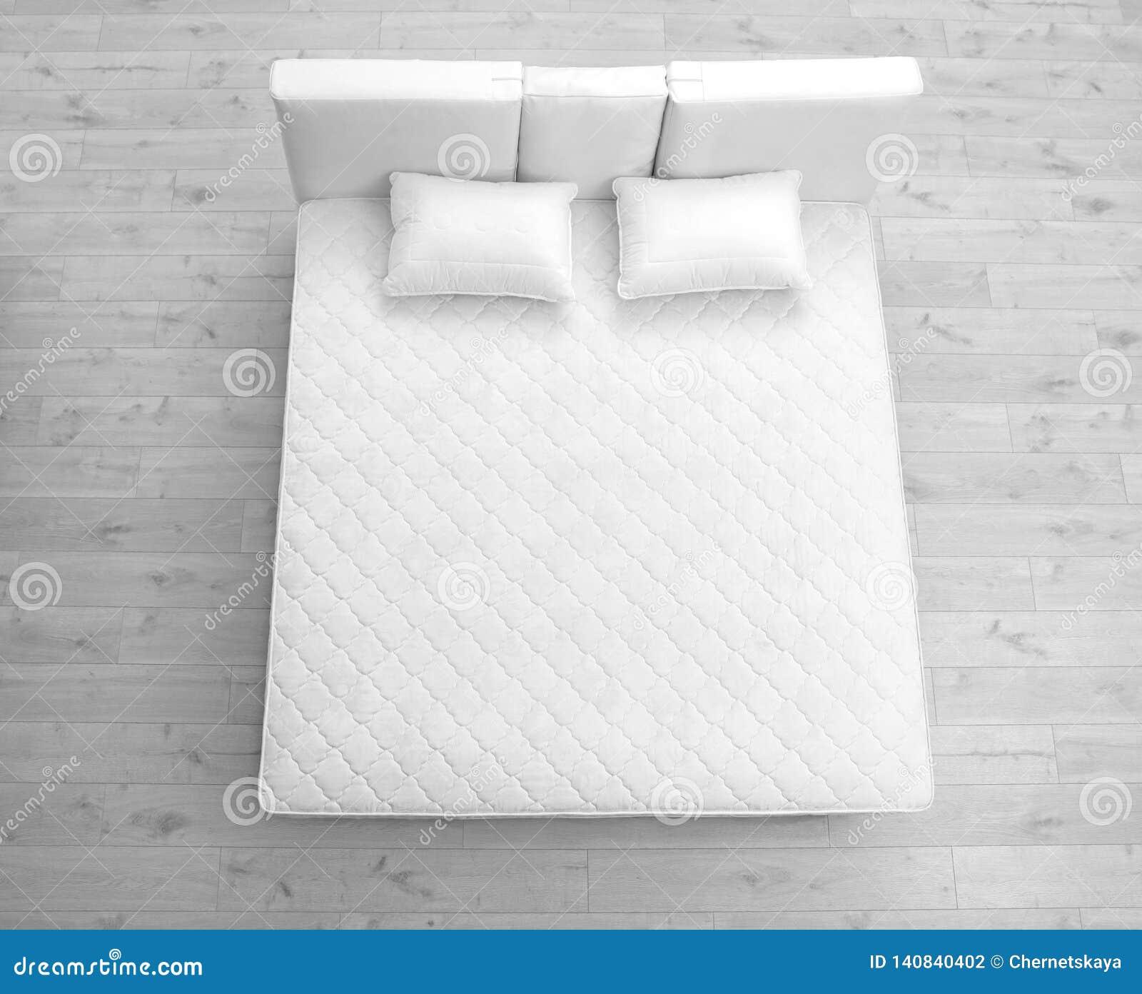 Comfortabel bed met nieuwe matras in ruimte, boven mening