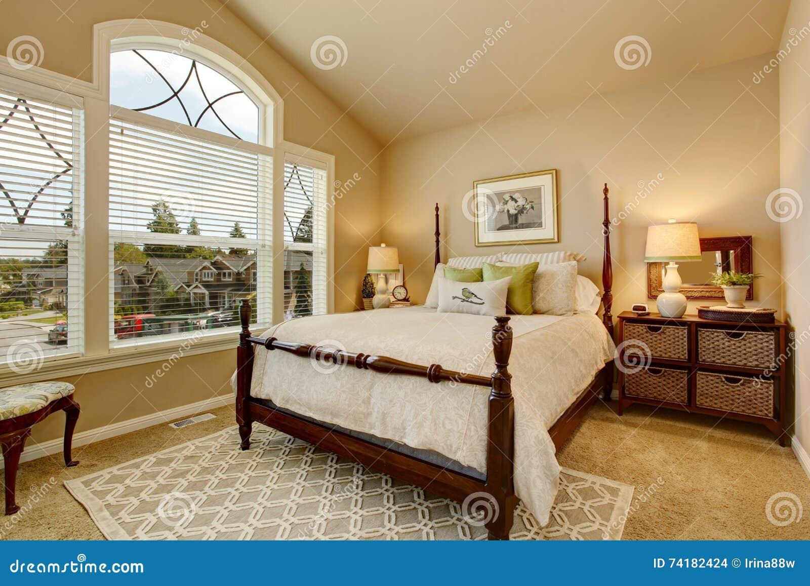 Comfortabele beige slaapkamer met gewelfd plafond en elegant ...