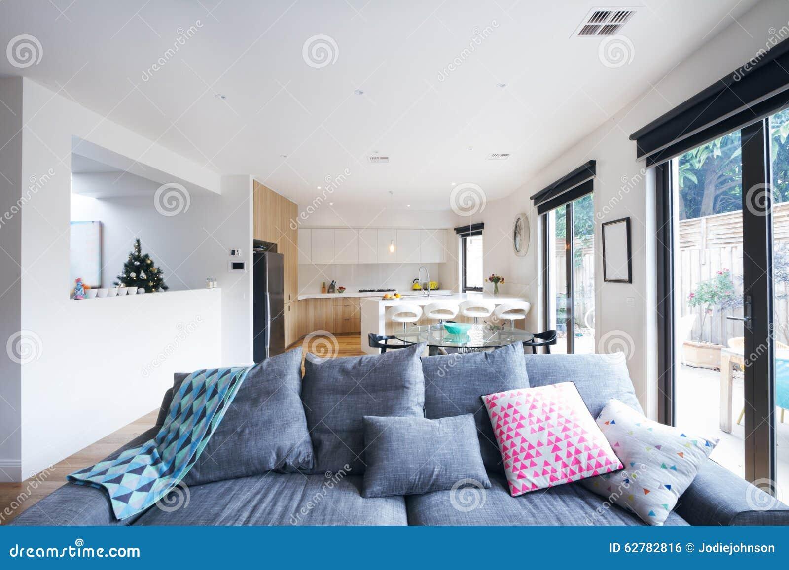 Comfortabele grijze bank in het open eigentijdse huis van de
