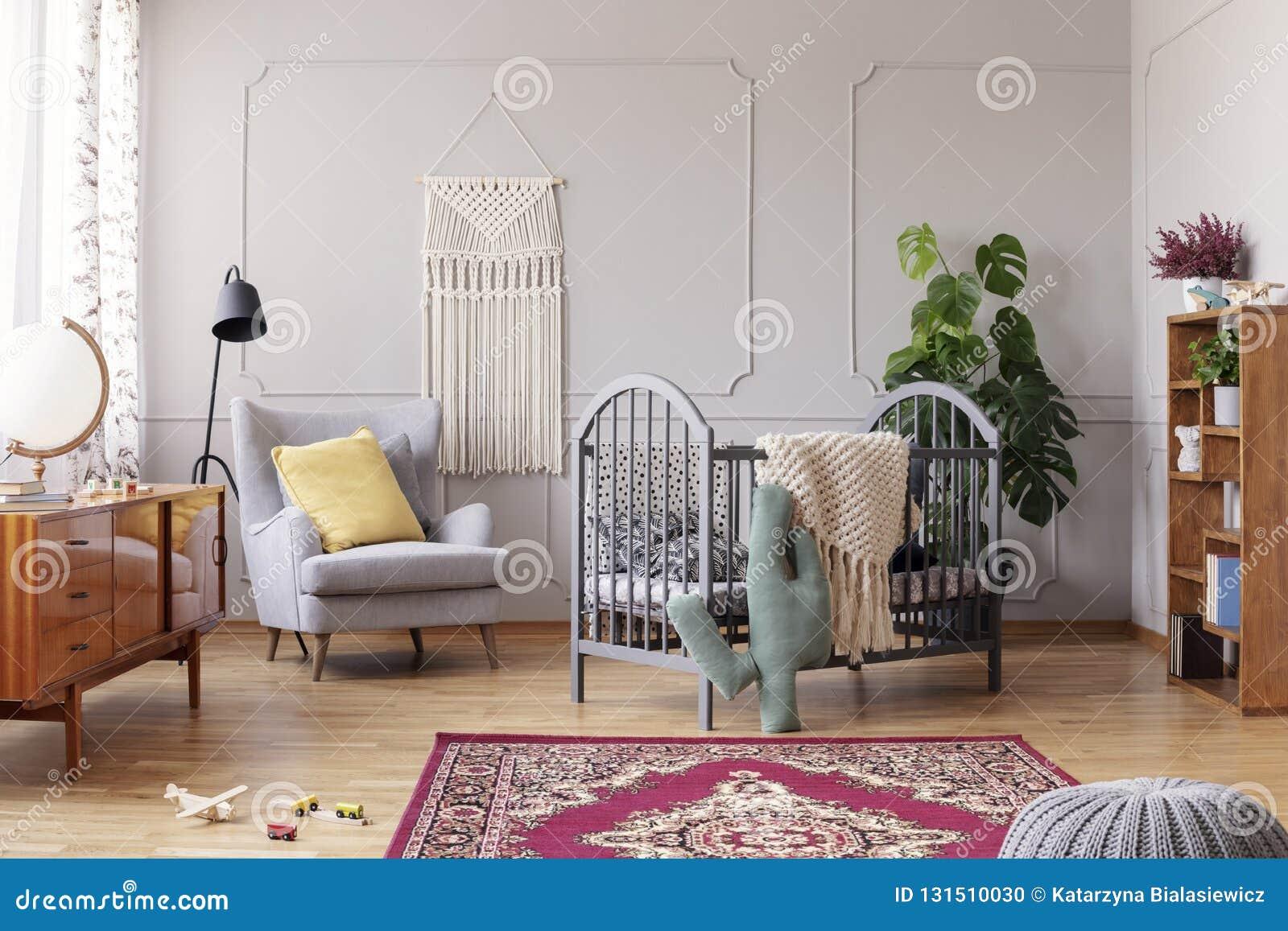 Comfortabele leunstoel en grijze houten voederbak, echte foto