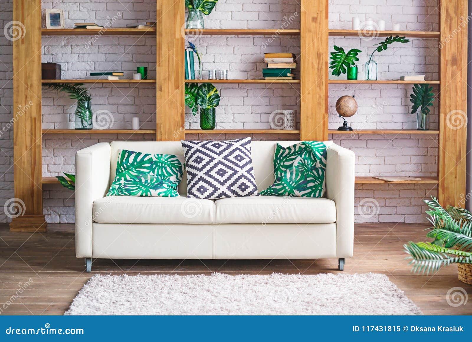 Comfortabele lichte ruimte met installaties, witte bank en modieus meubilair in Skandinavische stijl Woonkamer binnenlands concep