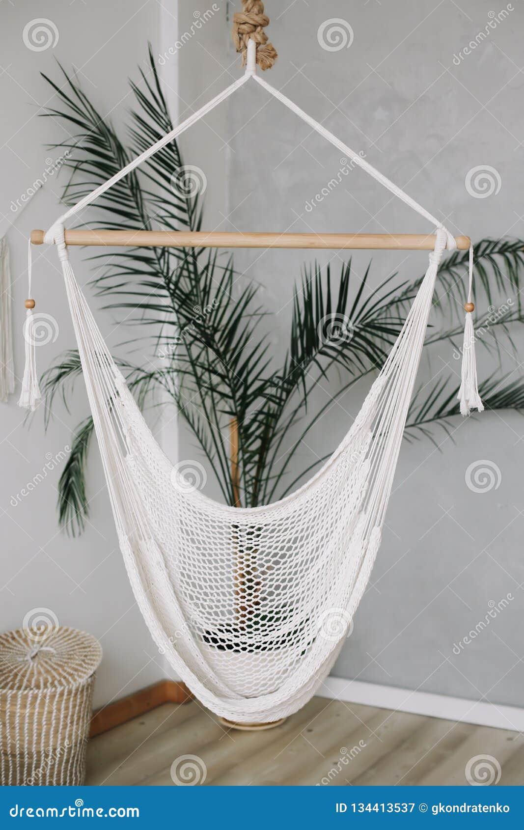 Comfortabele witte hangmat op het leven gebied, ontspannende hoek met palm thuis Minimaal huis binnenlands ontwerp
