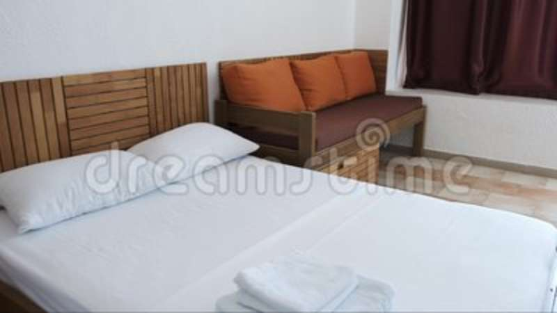 Phenomenal A Hotel Room With A White Double Bed Brown Sofa With Orange Cushions And Chocolate Curtains Caraccident5 Cool Chair Designs And Ideas Caraccident5Info