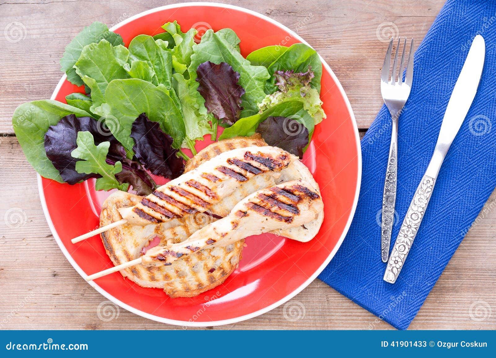 Comida asada a la parrilla servida con la ensalada
