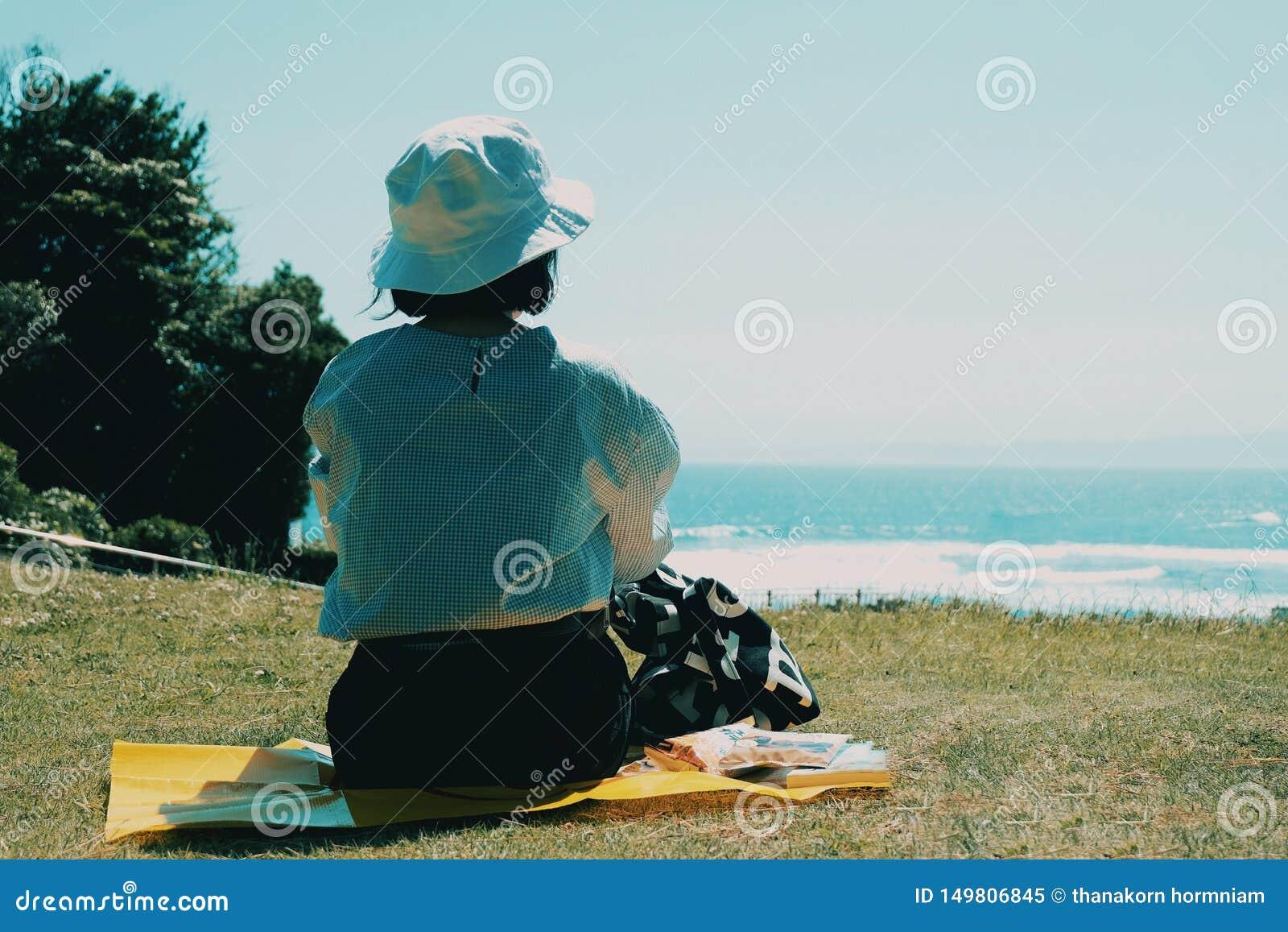 Comida campestre de la muchacha en el jardín de la playa