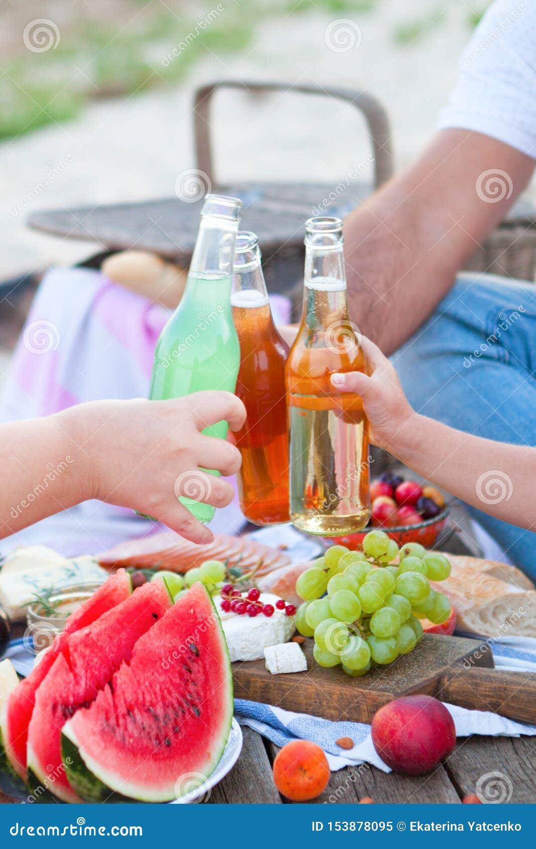 Comida campestre en la playa en la puesta del sol en el boho del estilo, la comida y el concepto de la bebida