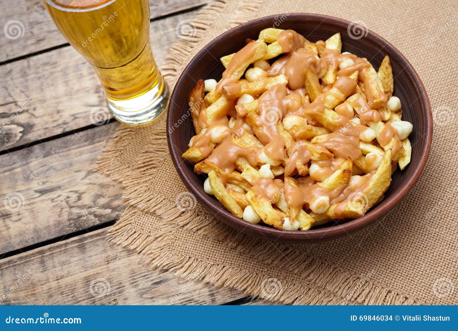 Comida canadiense de Poutine con las fritadas, el queso cuajado, la cerveza y la salsa