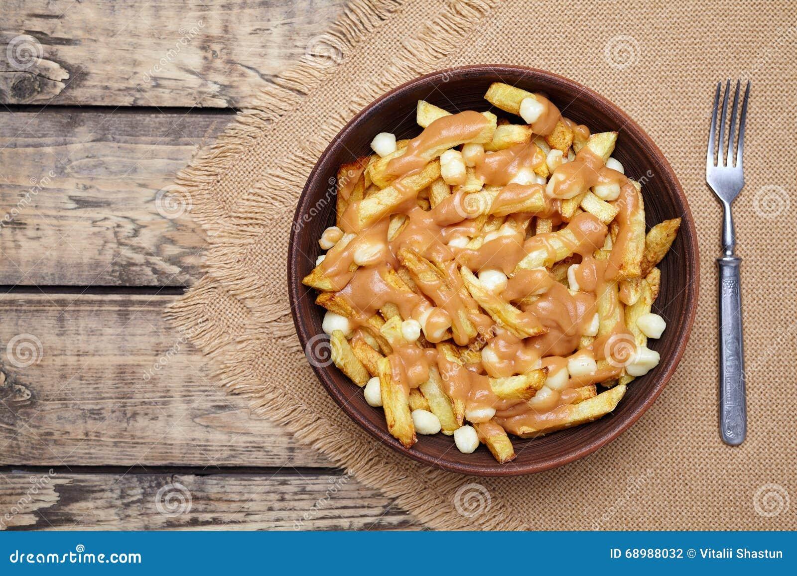 Comida canadiense tradicional de Poutine con las fritadas, el queso cuajado y la salsa