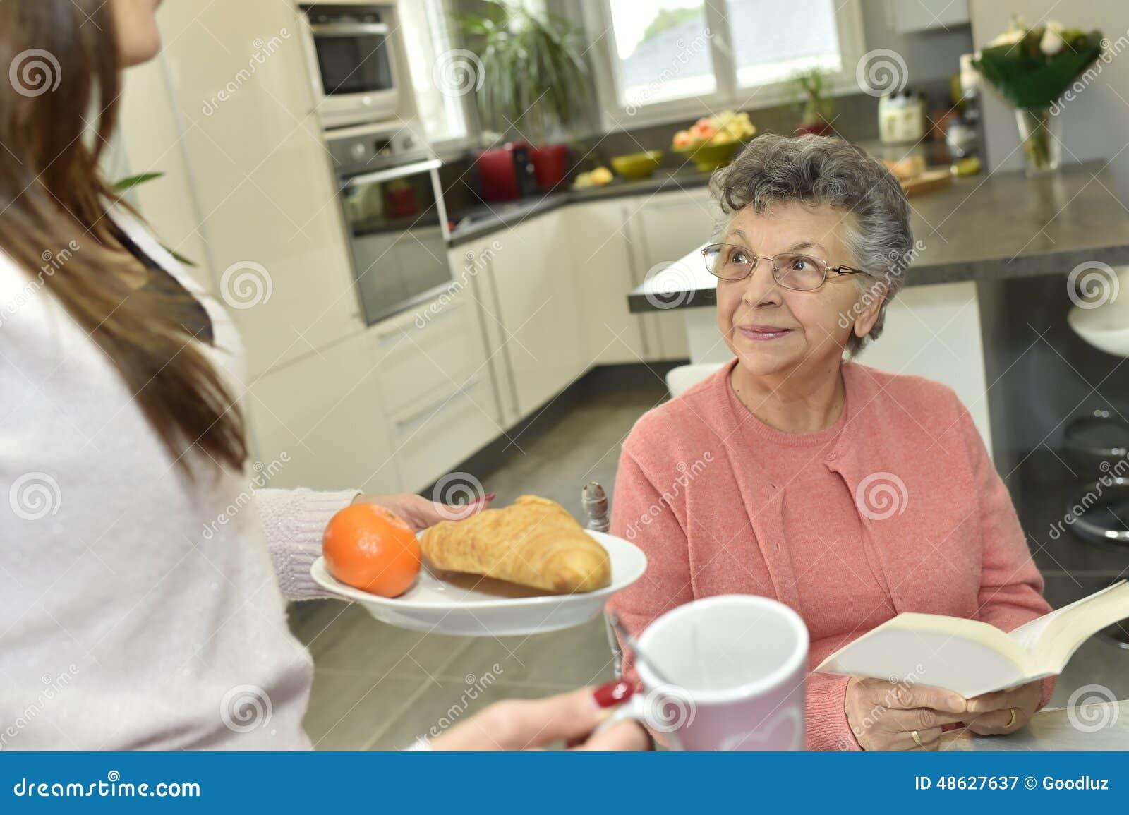 Comida casera de la porción del cuidador a una mujer mayor