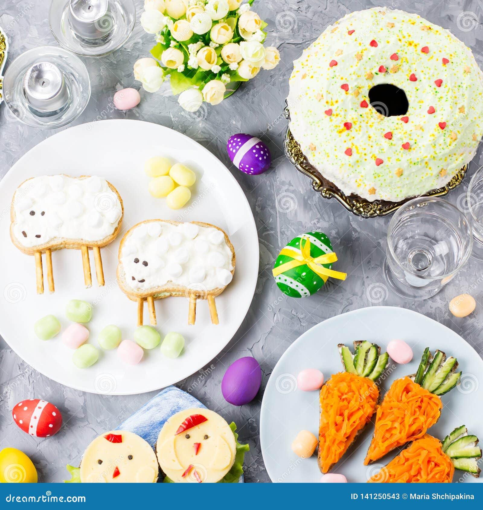 Comida colorida divertida de Pascua para los niños con las decoraciones en la tabla Concepto de la cena de Pascua