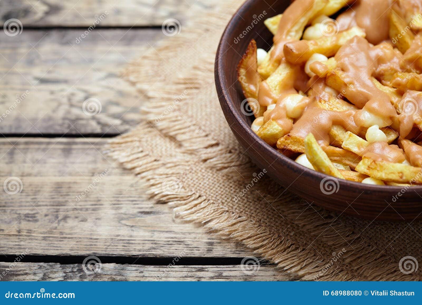 Comida de alimentos de preparación rápida tradicional hecha en casa canadiense de Poutine con las fritadas