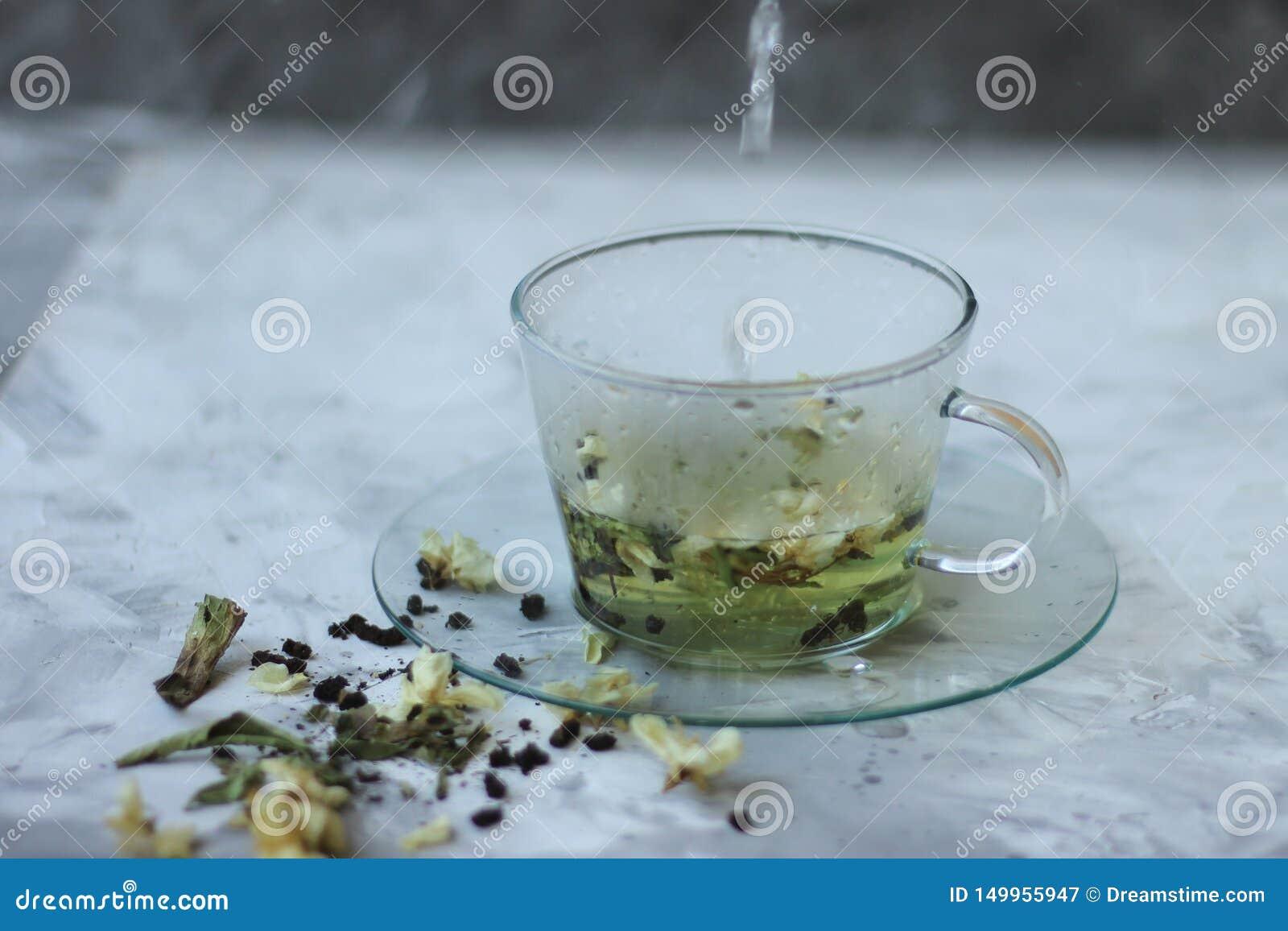 Comida del Detox y beber concepto healfhy de la forma de vida Taza de cristal de té verde con el jazmín en un fondo gris cierre