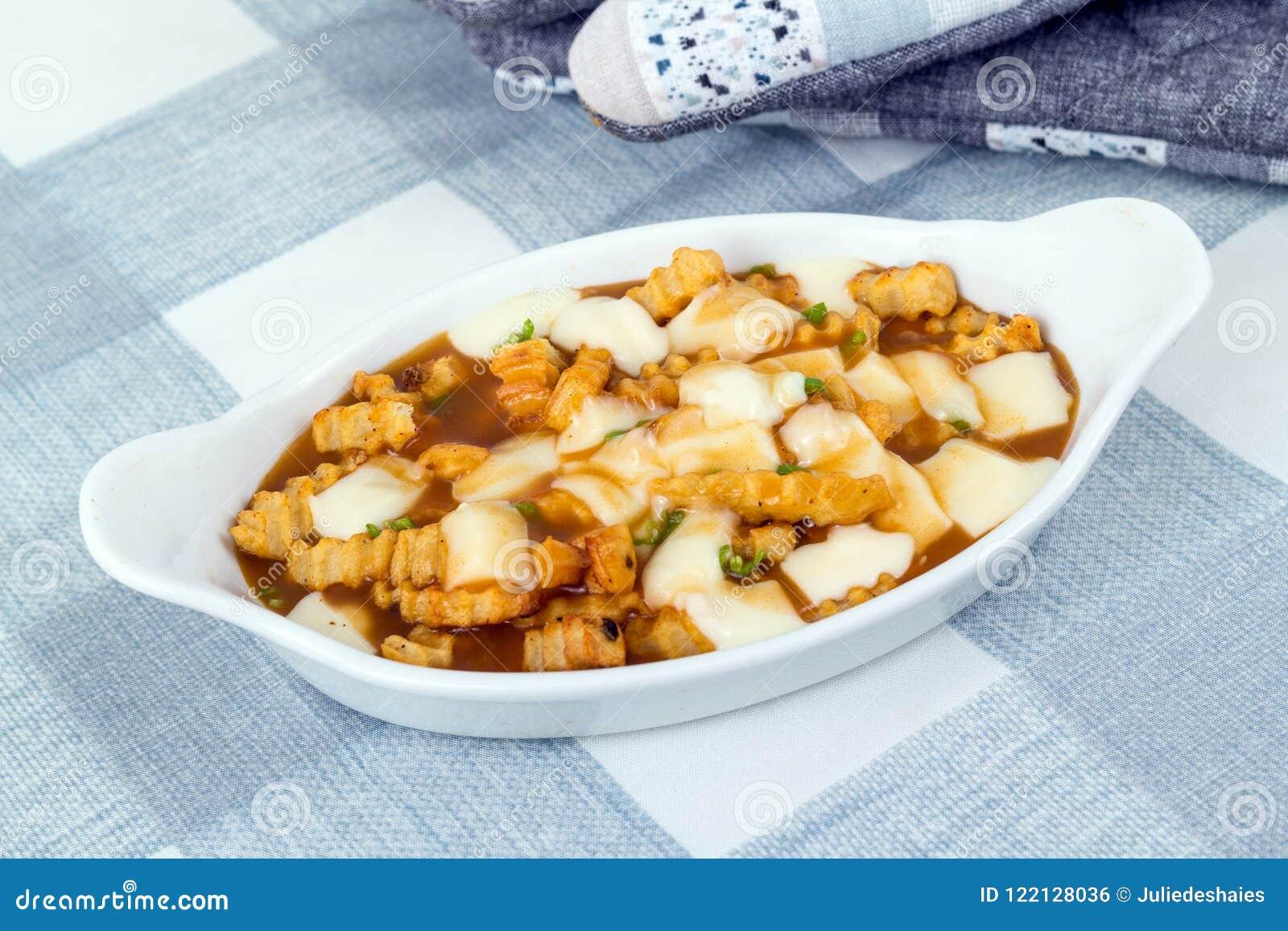 Comida deliciosa del poutine del restaurante en la comida canadiense mA del mantel