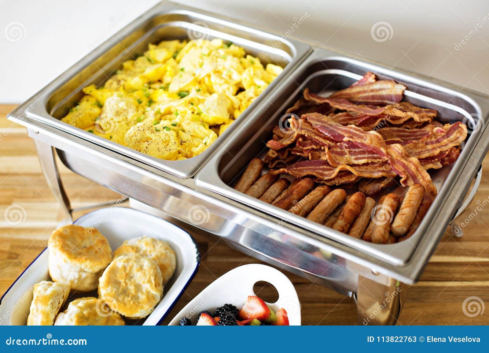 Comida fría del desayuno con los huevos revueltos y el tocino
