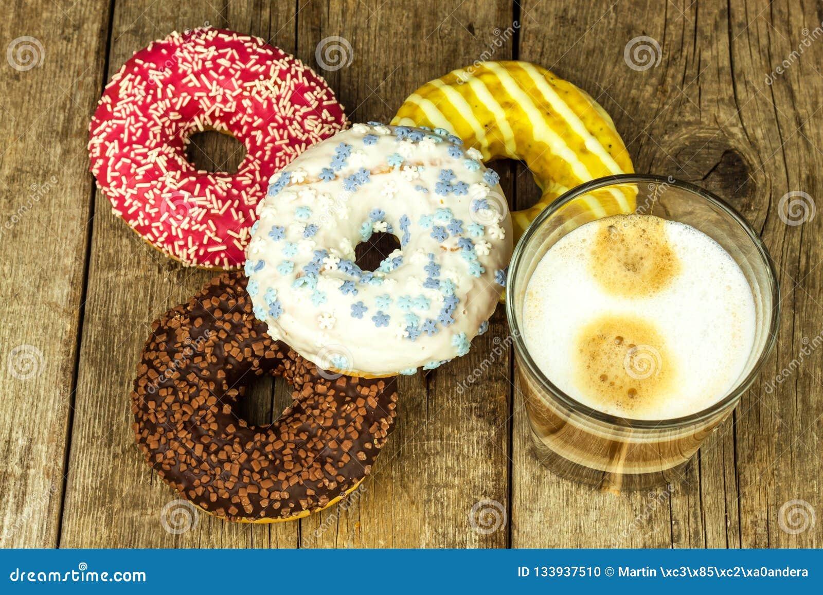Comida malsana Anillos de espuma en una tabla de madera Café al postre Peligros de la obesidad y de la diabetes Ventas de dulces