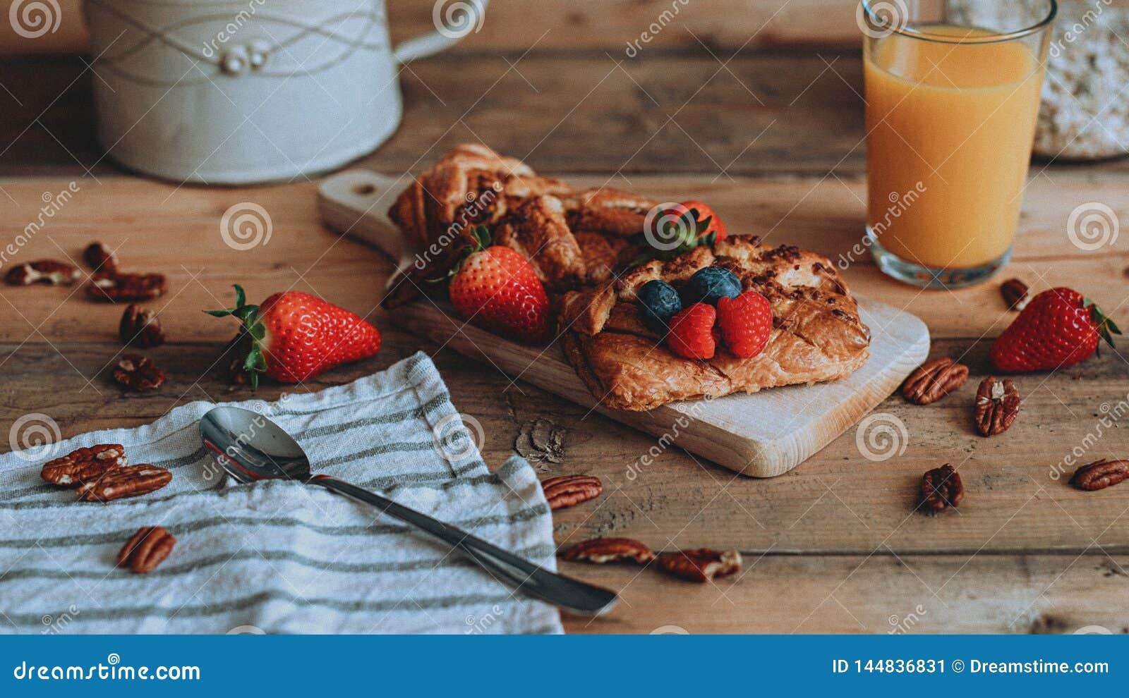 Comida que diseña los pasteles dulces con la fruta en los tablones de madera