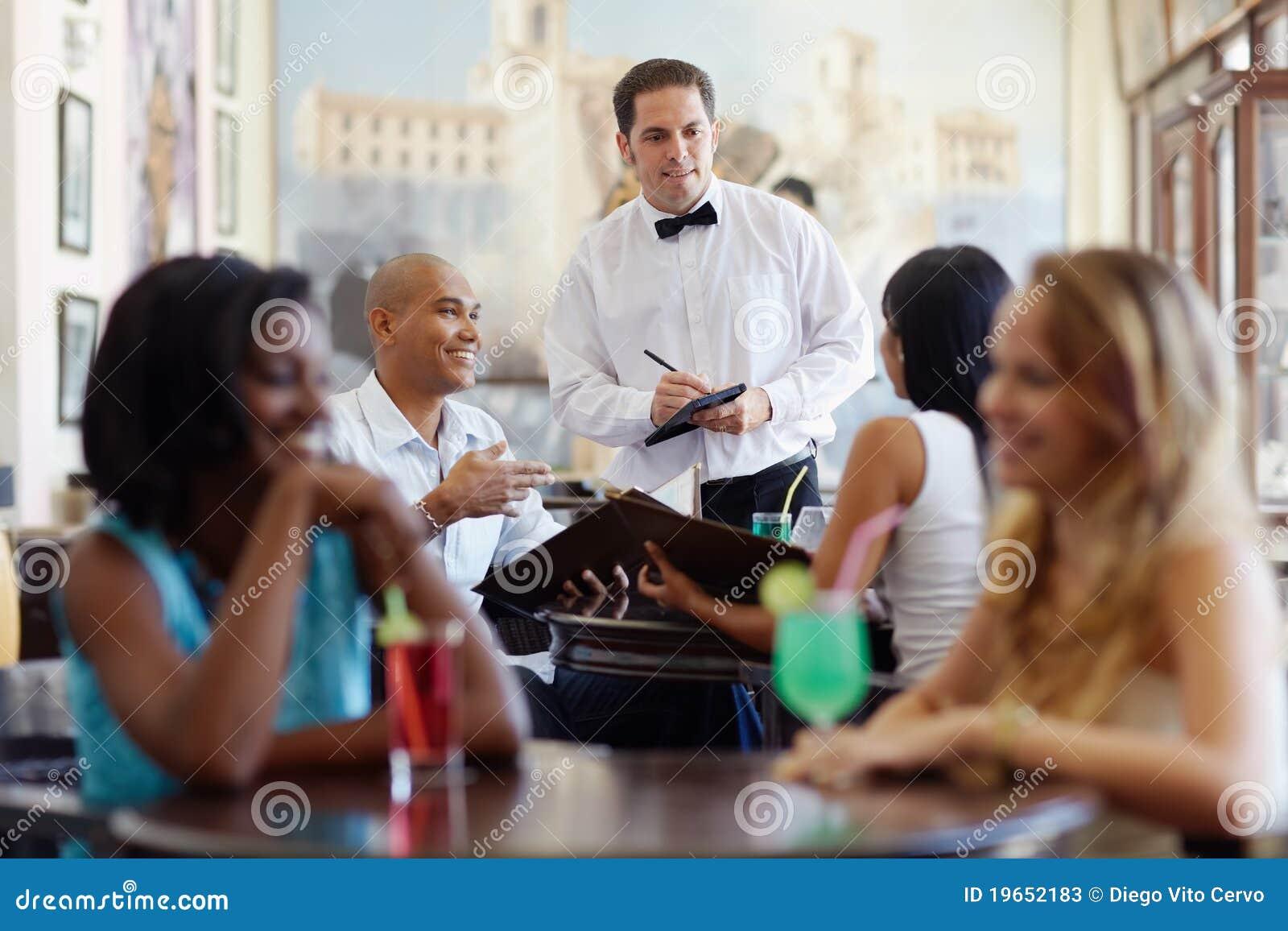 Comida que ordena de la gente al camarero en restaurante