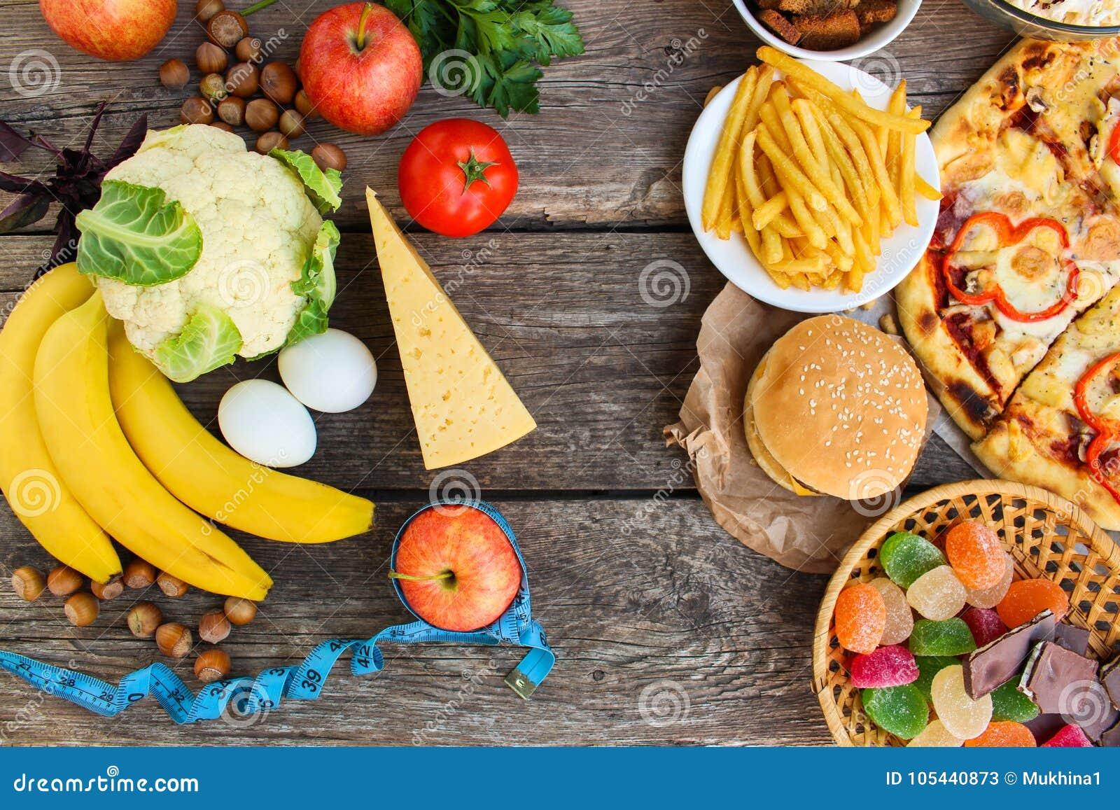 Comida rápida y comida sana en viejo fondo de madera Concepto que elige la nutrición correcta o de la consumición de los desperdi