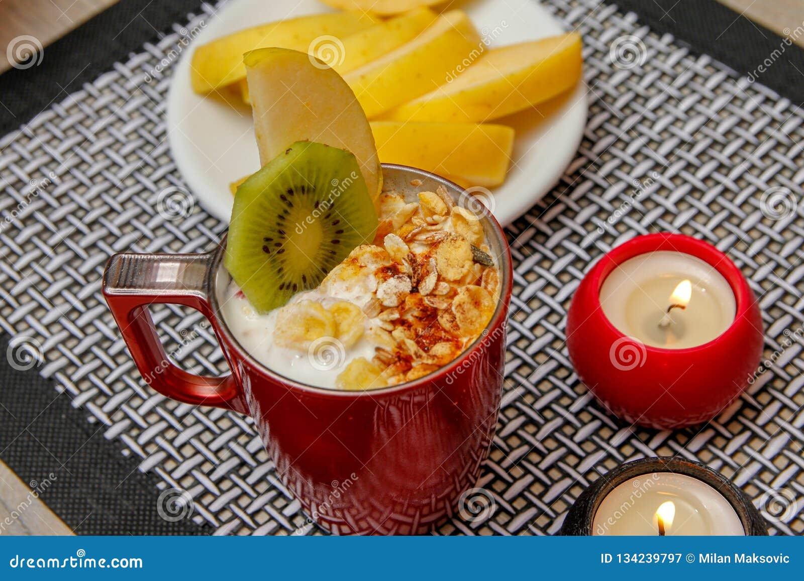Comida sana, diversas semillas, cereales integrales y frutas secadas en yogur Fruta fresca, manzana, kiwi y caqui